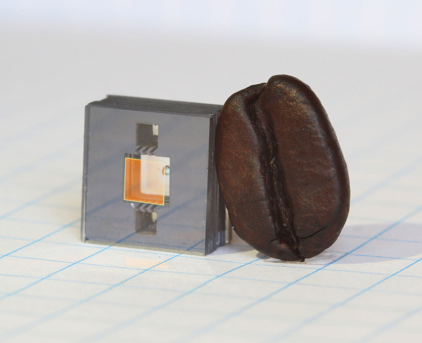 small atomic clock with coffee bean for scale