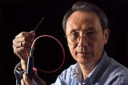 Xiao Tang of NIST's Information Technology Laboratory holding up an optical fiber channel