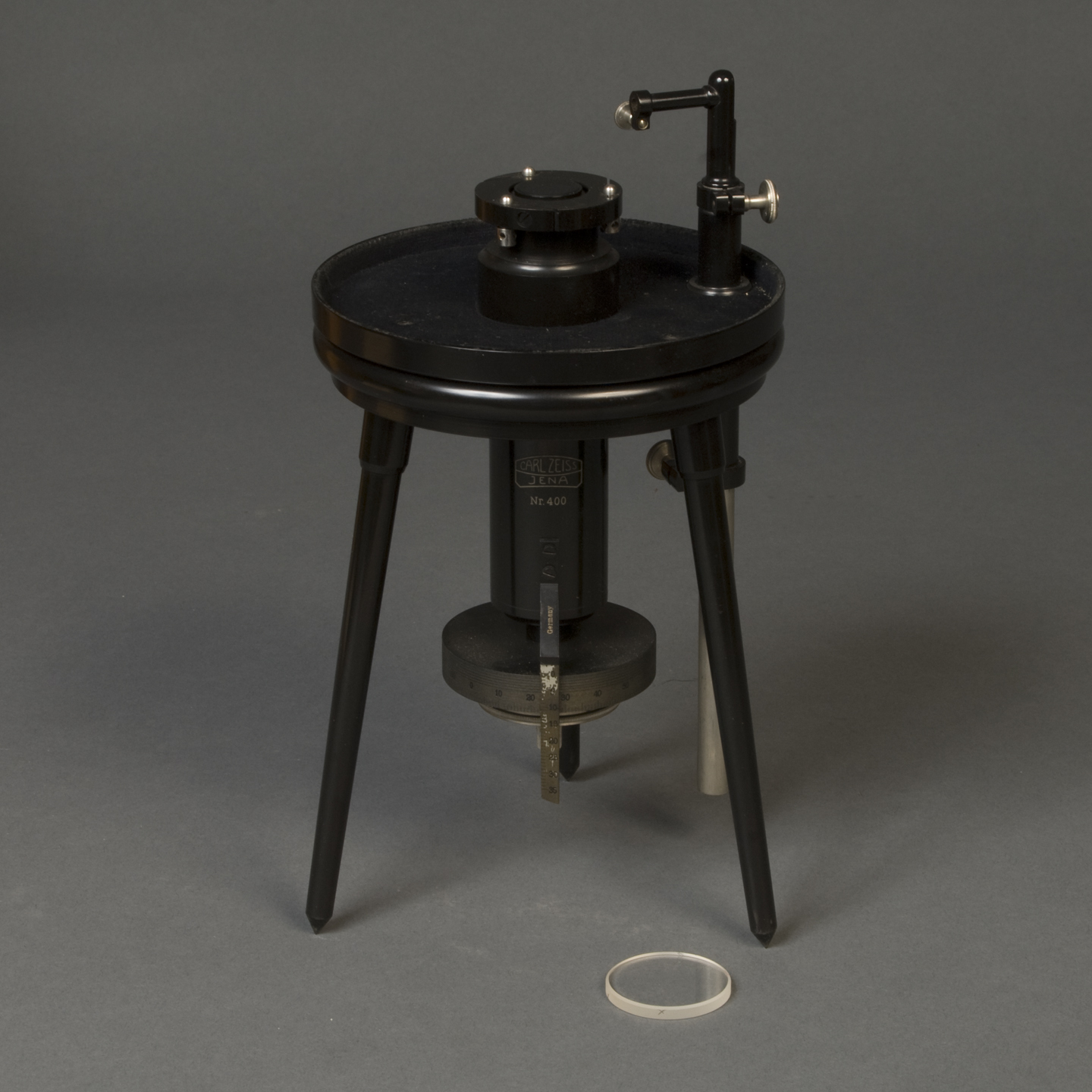 "tripod device with lens. The words ""Carl Zeiss, Jena, Nr. 400"" appear on a cylinder that extends below the tripod's platform. Below that is a graduated dial, presumably for raising and lowering the platform."