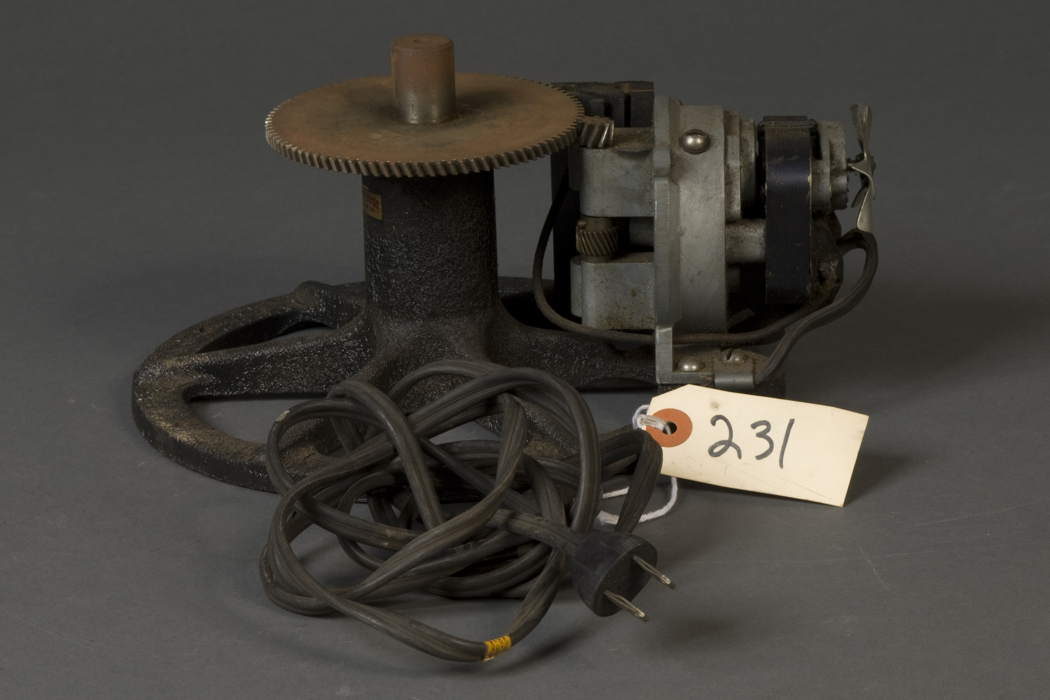 "geared mechanism with an electric plug. Attached to the plug's wire is a tag that reads ""231."" The device is geared to another smaller gear on a device with what looks like a flywheel coming from the front of it."