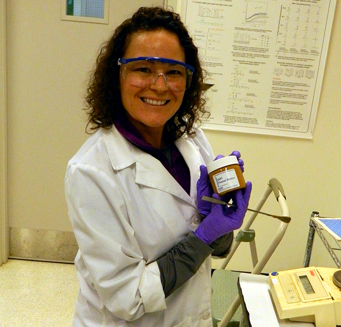 NIST chemist Carolyn Burdette in a white lab coat and wearing goggles holding up a jar of  SRM 2387, Peanut Butter