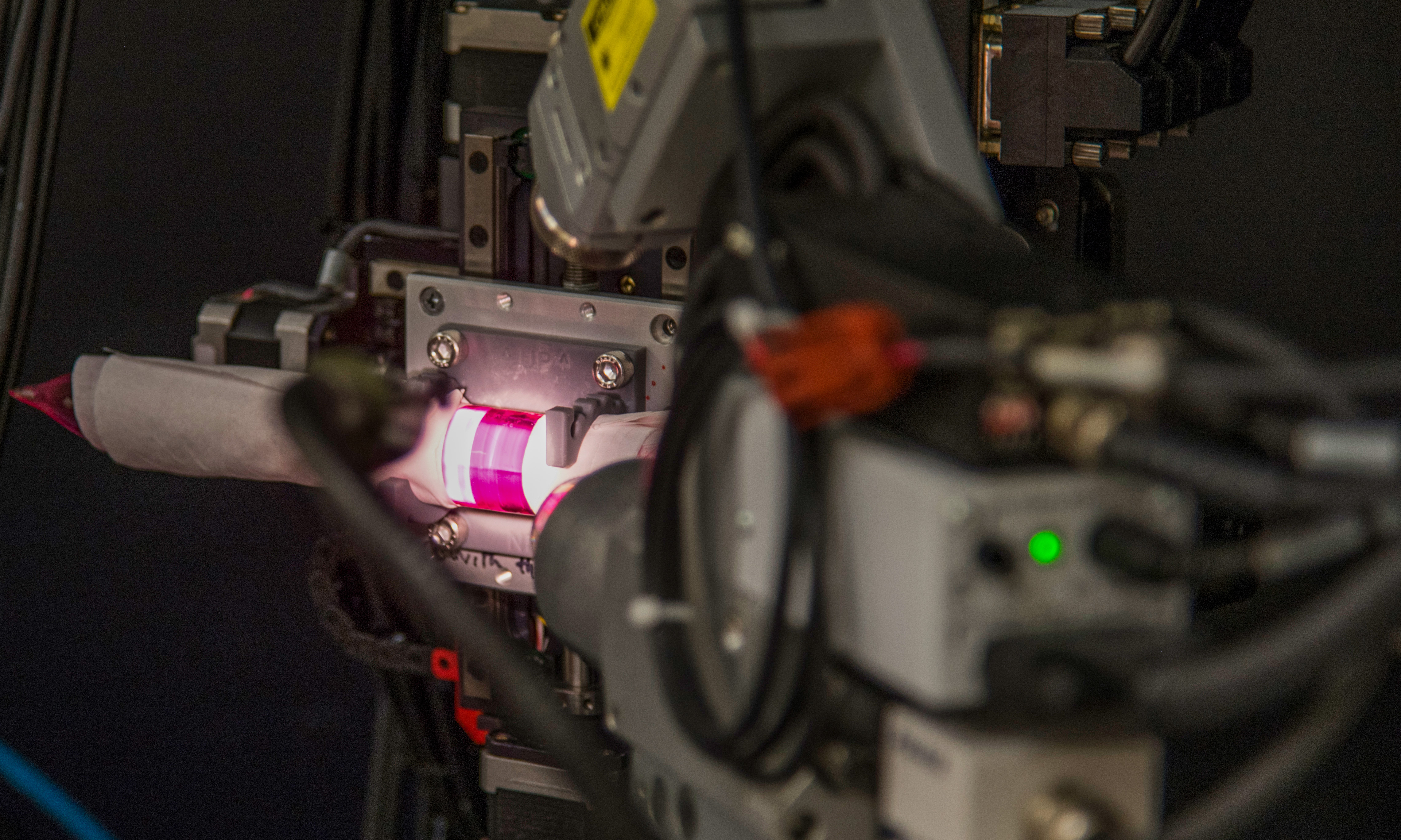 A ruby colored rod, wrapped in tissue paper and illuminated by a bright light, mounted inside an X-ray diffraction machine