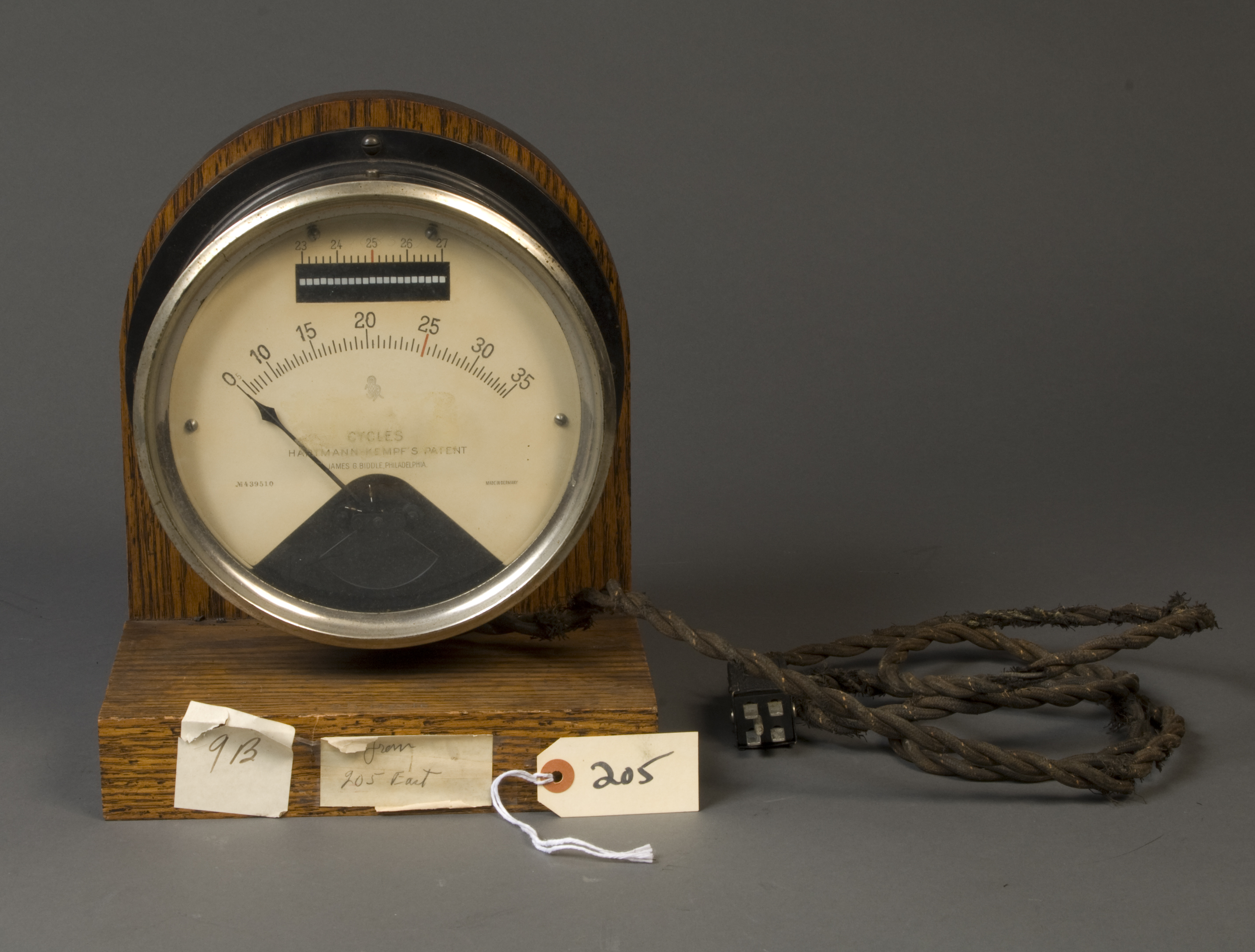 "A wood-framed circular face with a line gauge reading from 0 to 35 in 1/2 increments with a red line at 25. Another gauge above goes from 23 to 27, also with a red line at 25. Words read ""cycles,"" Hartmann-Kempf's Patent"" and James G. Biddle Philadelphia."