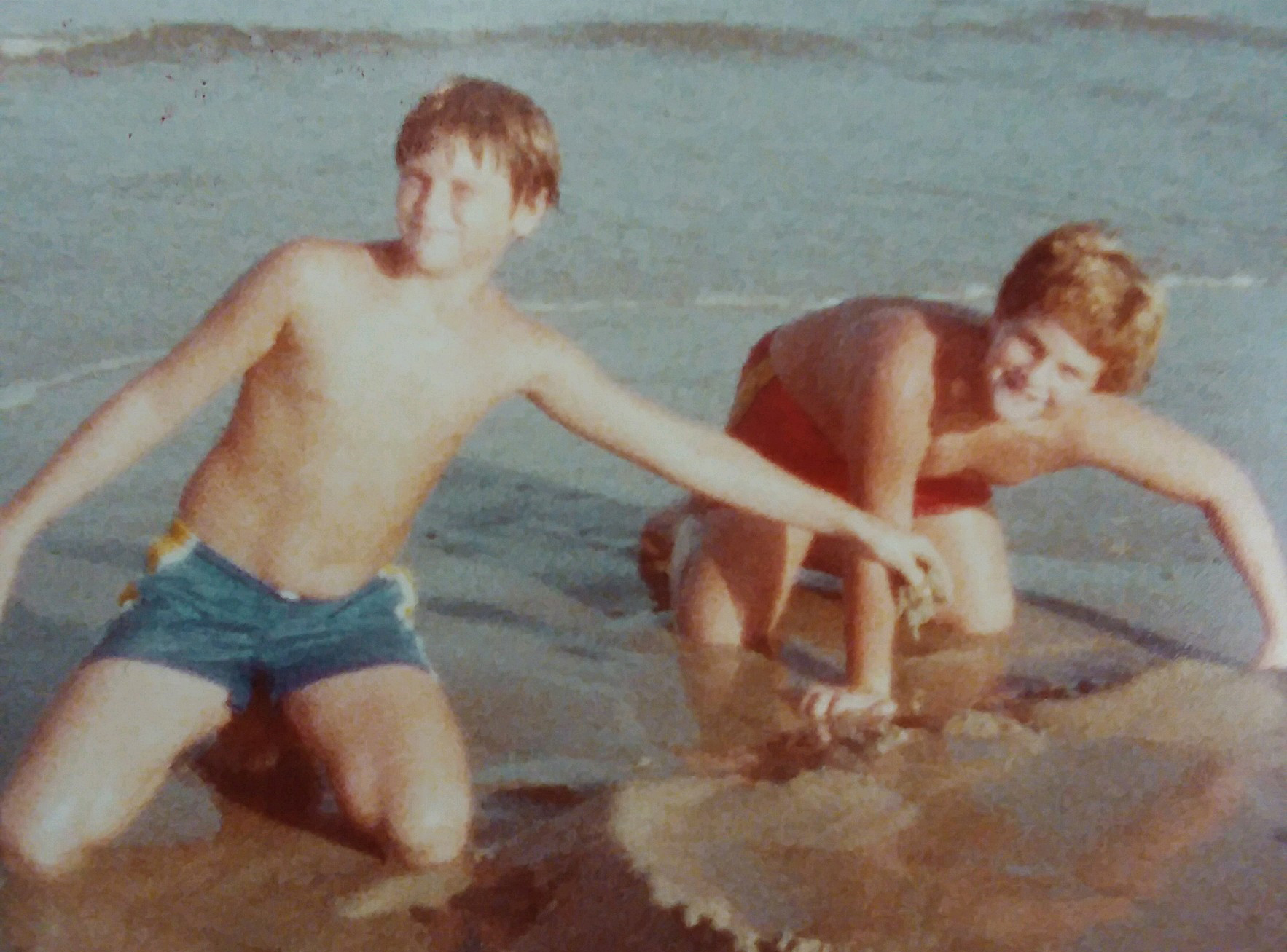 two smiling young boys playing in the sand at the beach