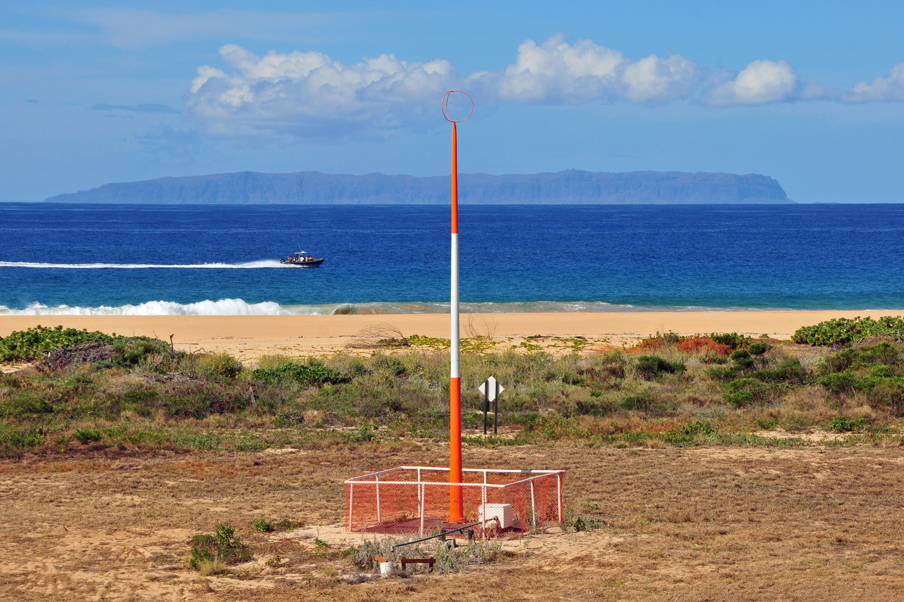 An orange and white antenna a few meters away from a beach. A boat speeds past in the distance. Beyond that the island of Niihau is visible.