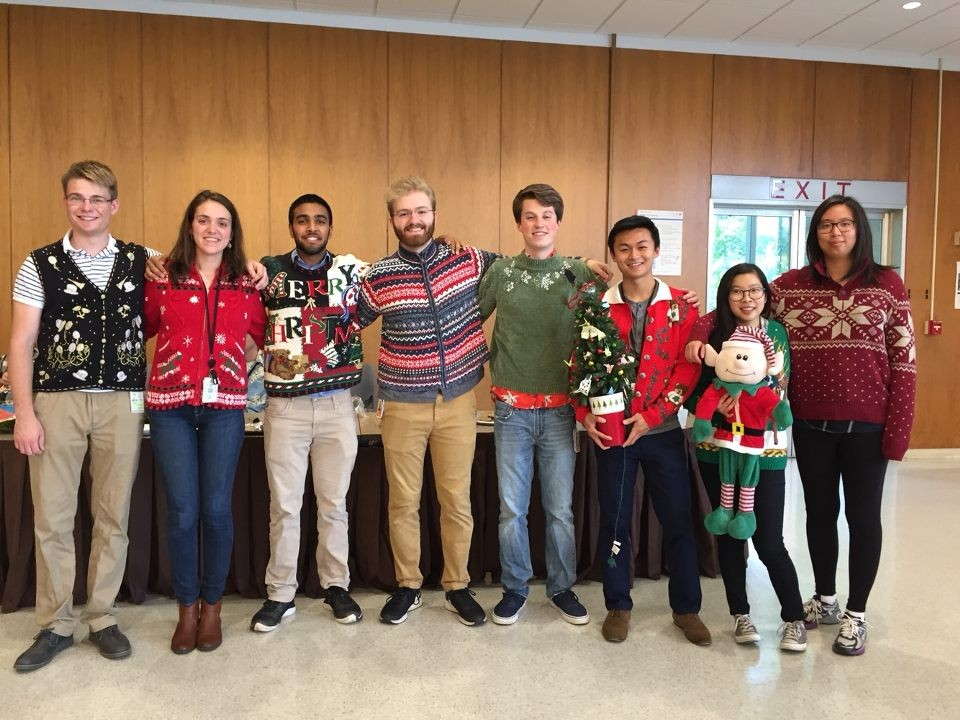 group of young men and women posting in their Christmas and winter-themed sweaters.