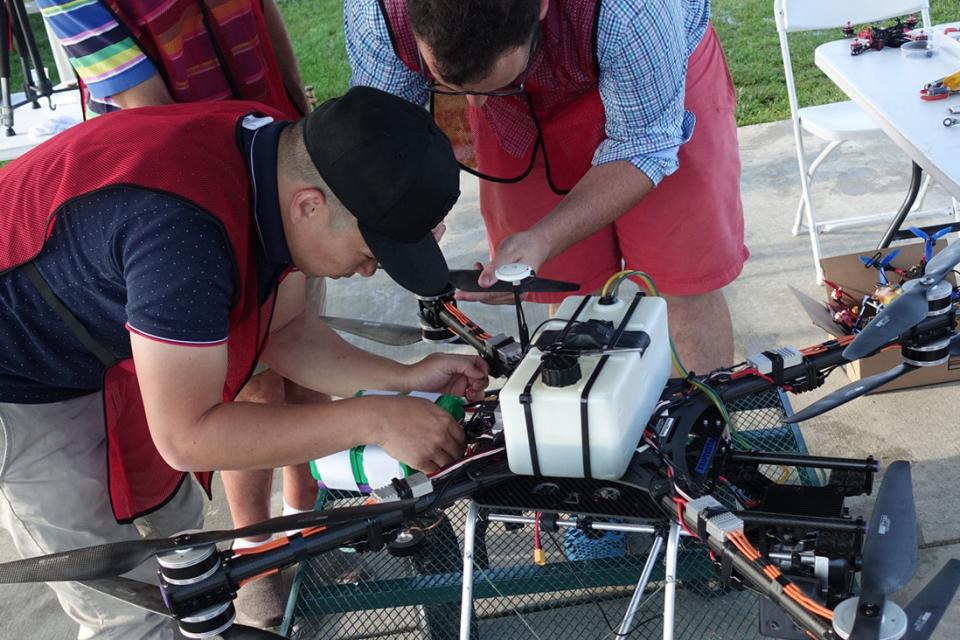 Two men in red smocks make adjustments to their drone