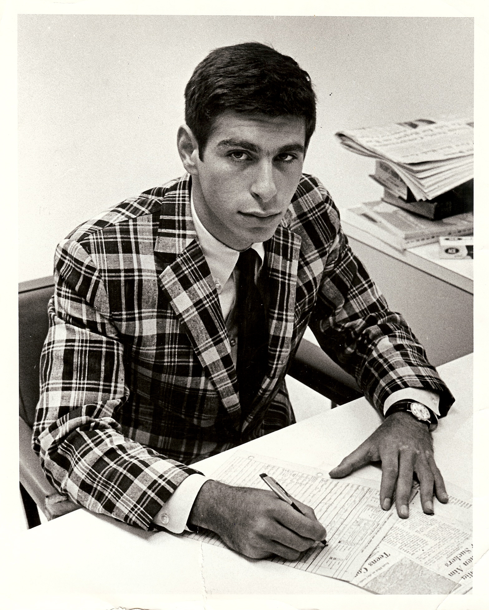 A young Mark Stolorow in a plaid jacket sitting at a desk