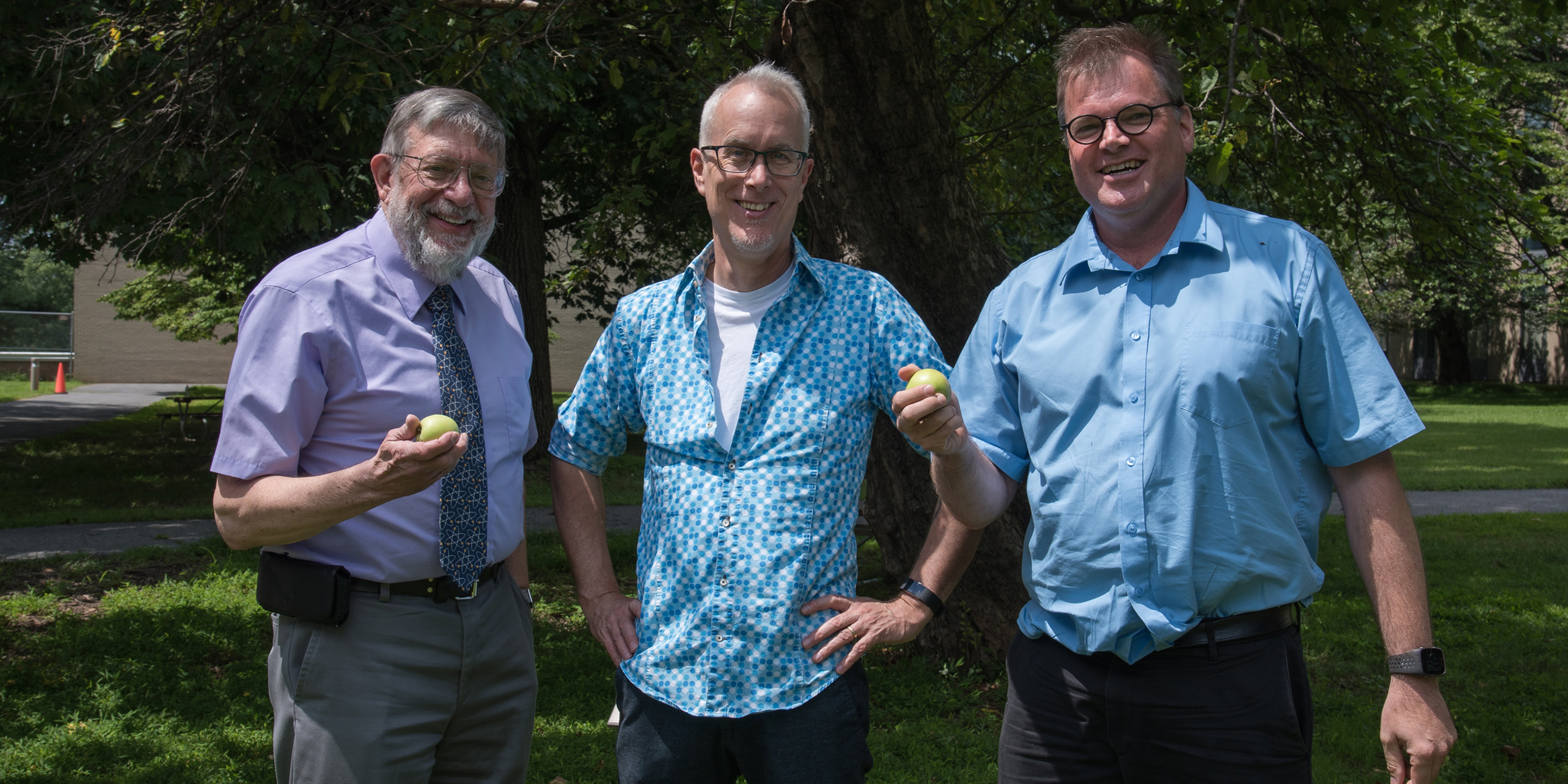 Bill Phillips, Jon Pratt and Stephan Schlamminger smile before the Newton apple tree on the NIST Gaithersburg campus. Bill and Stephan are holding small apples from the tree.