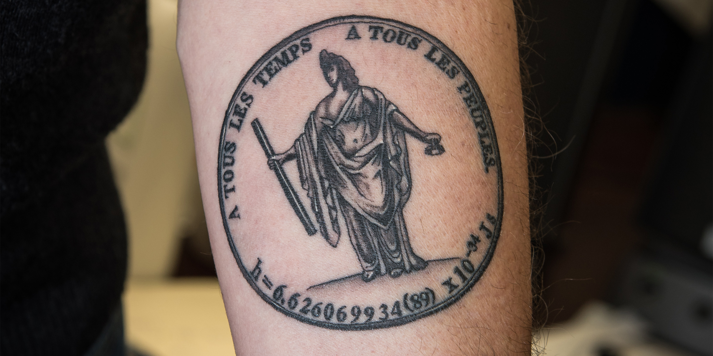 "Jon Pratt shows off a tattoo featuring a statue holding a meter bar and a kilogram artifact. The words ""For all times, for all peoples"" are written in French above, and the final value for the Planck constant is written below."
