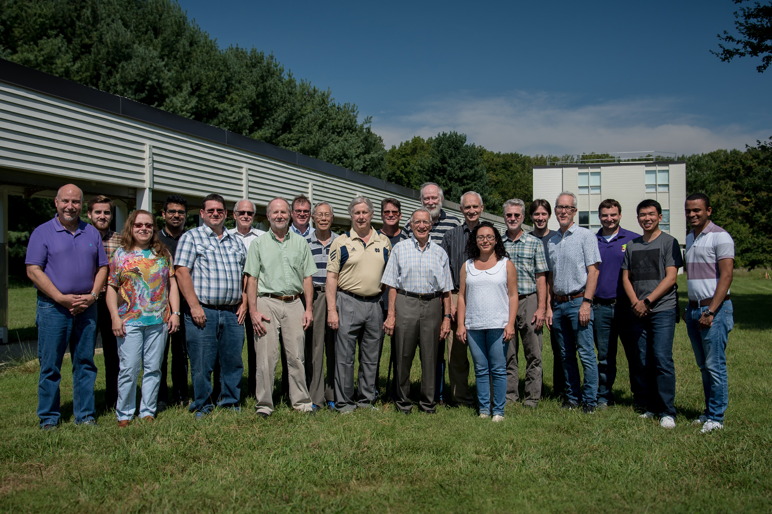 Group of researchers standing in a field in front of a small lab
