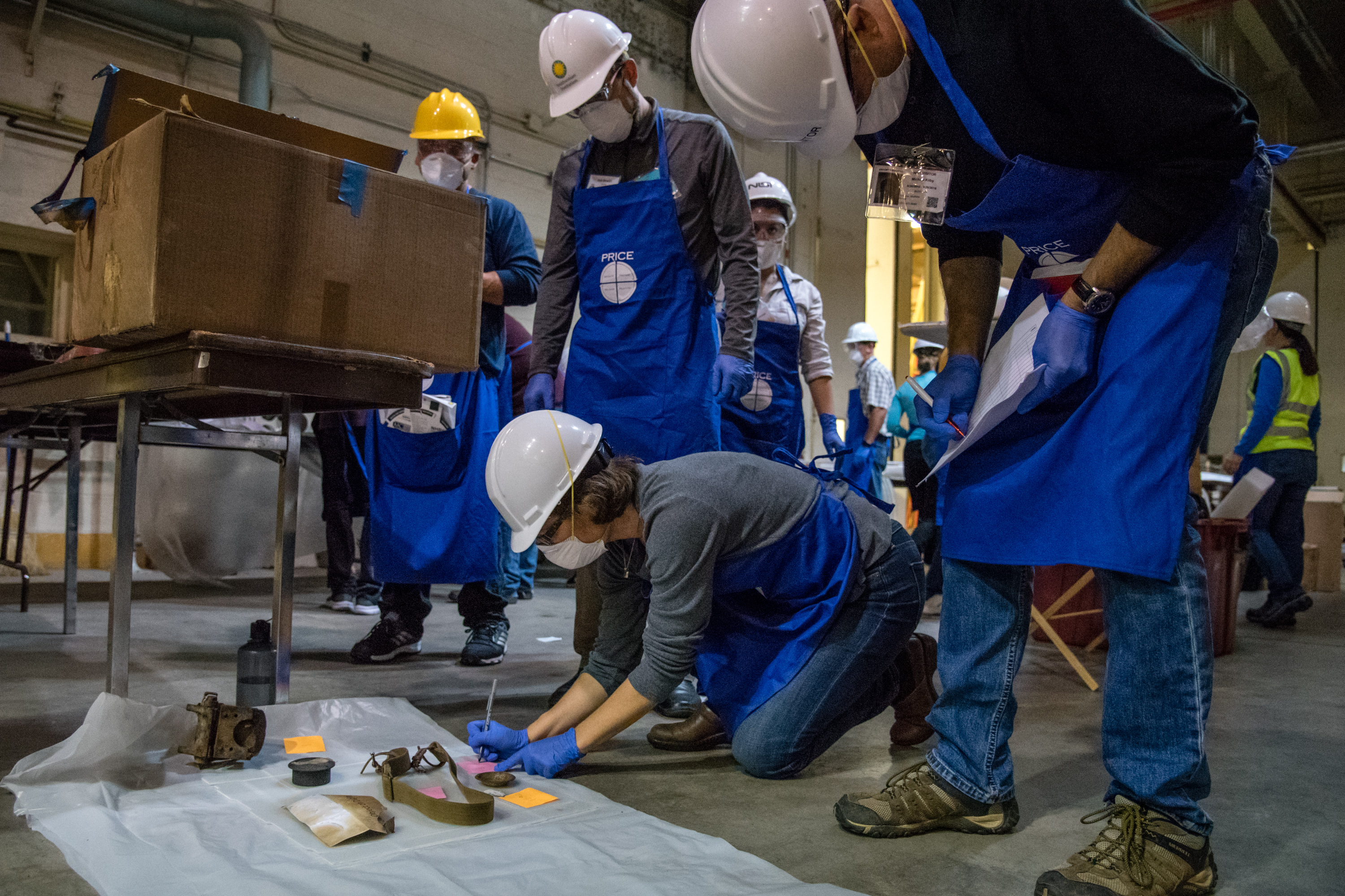 Smithsonian employees wearing hard hats, blue smocks, and respirators kneel over artifacts and record them on their clipboards