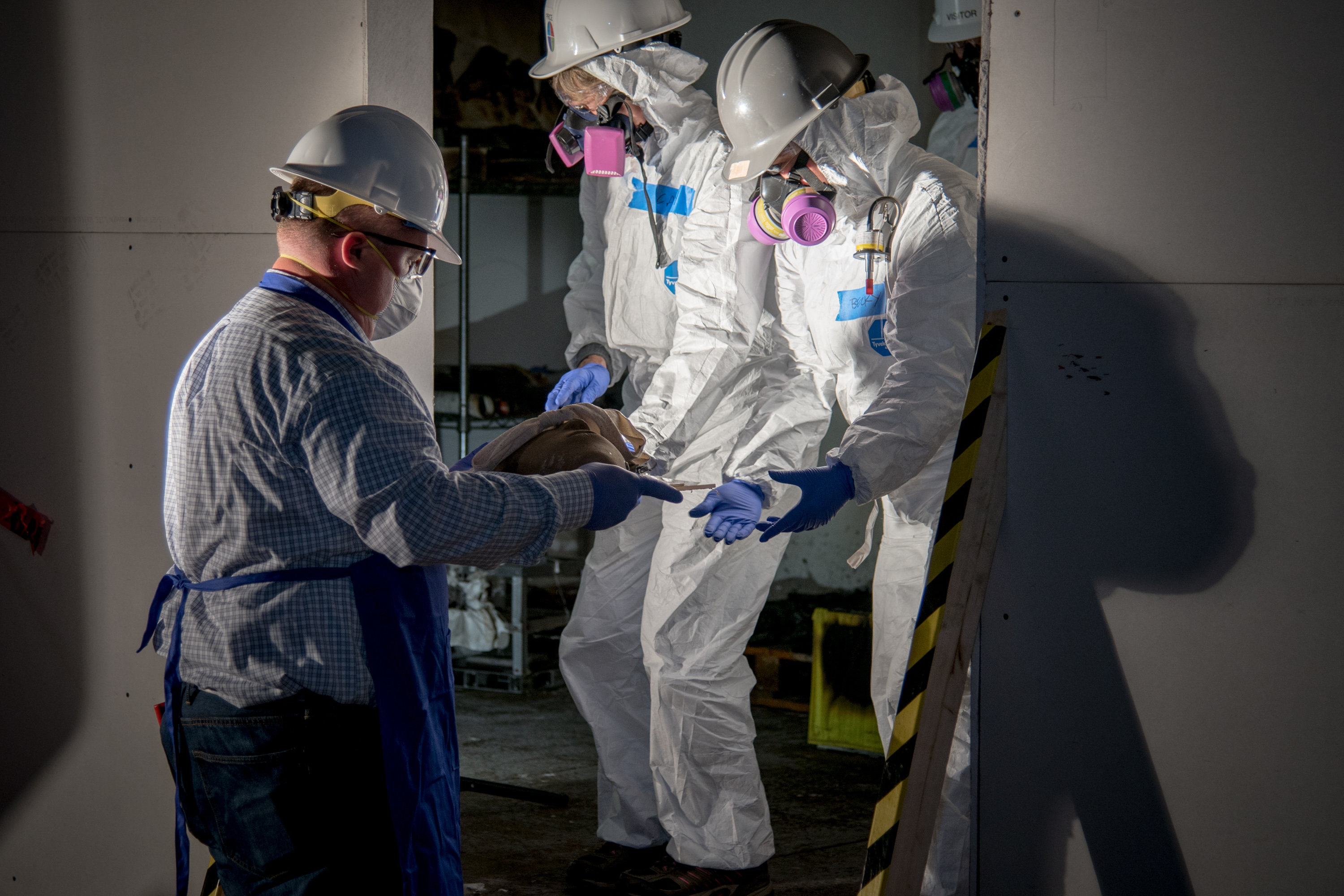 People wearing full body white hazard suits, hard hats, safety glasses and face masks emerge from burn test room with clay mask artifact