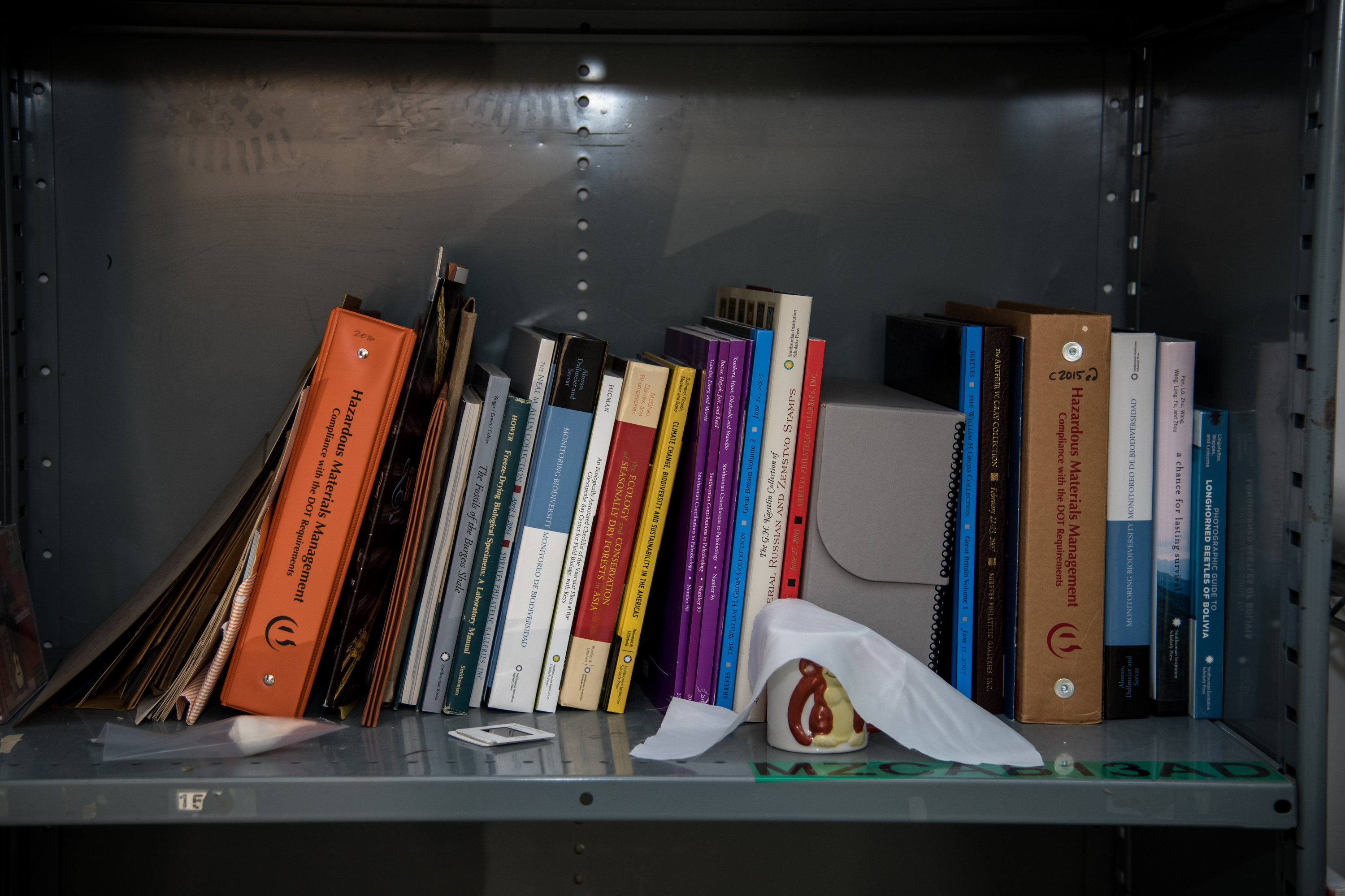 a shelf with books, folders and a small white ceramic mug with a monkey on it