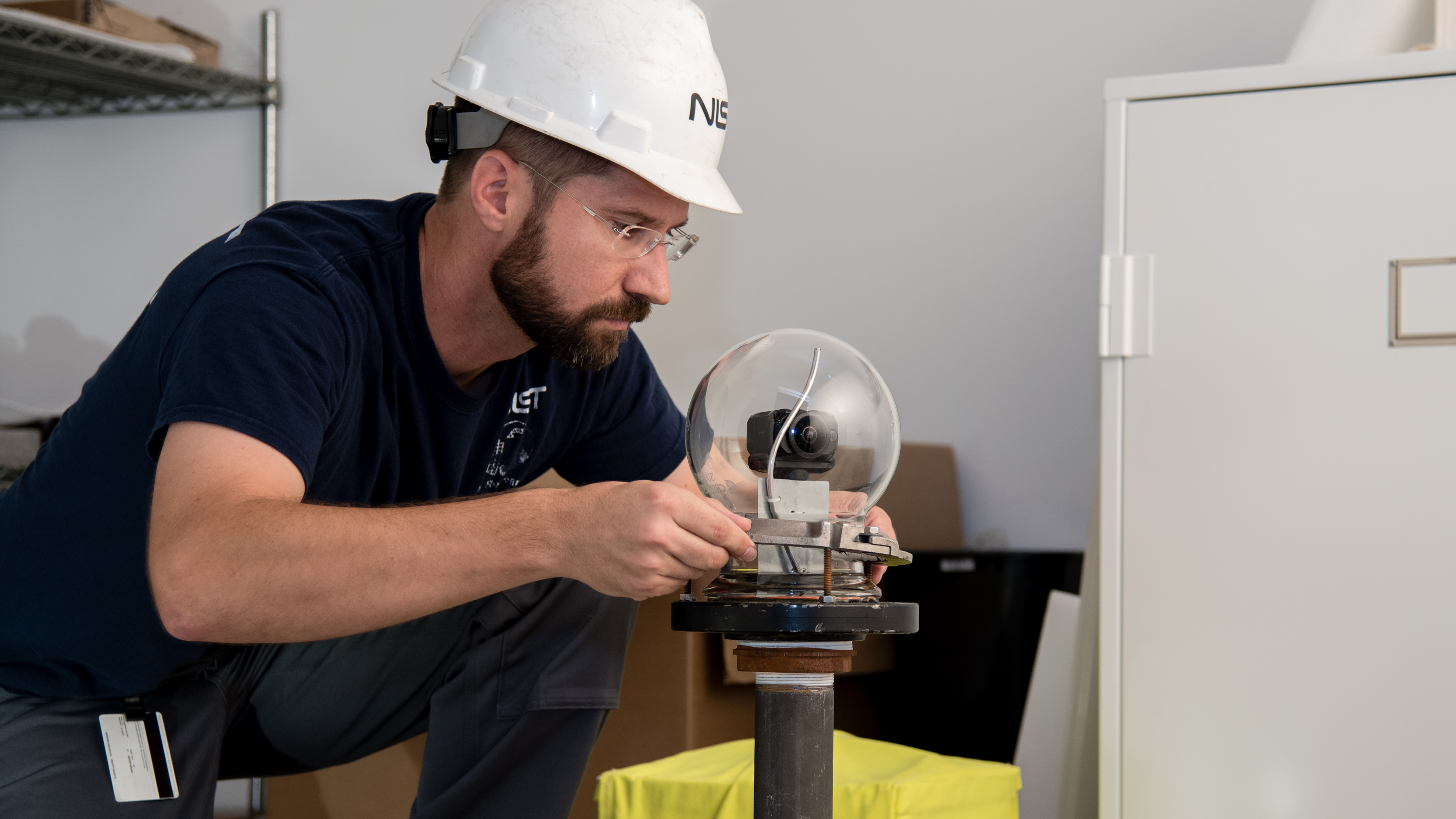 man with a beard, safety glasses, hard hat and blue shirt places a glass bubble over the top of a camera mounted on a steel pole inside the test room