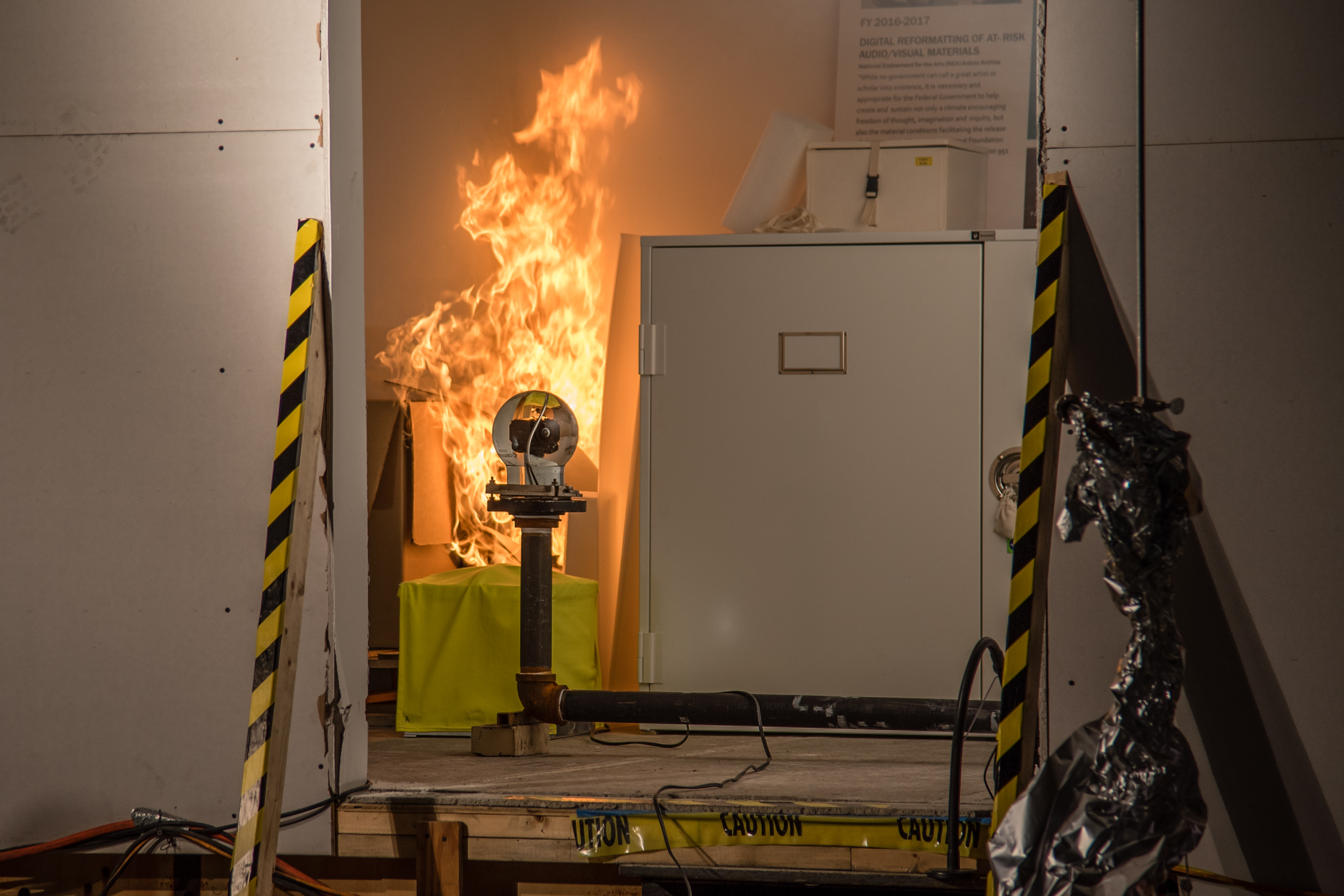 view through the doorway of the simulated storage room. The fire grows as a video camera in the room looks on.