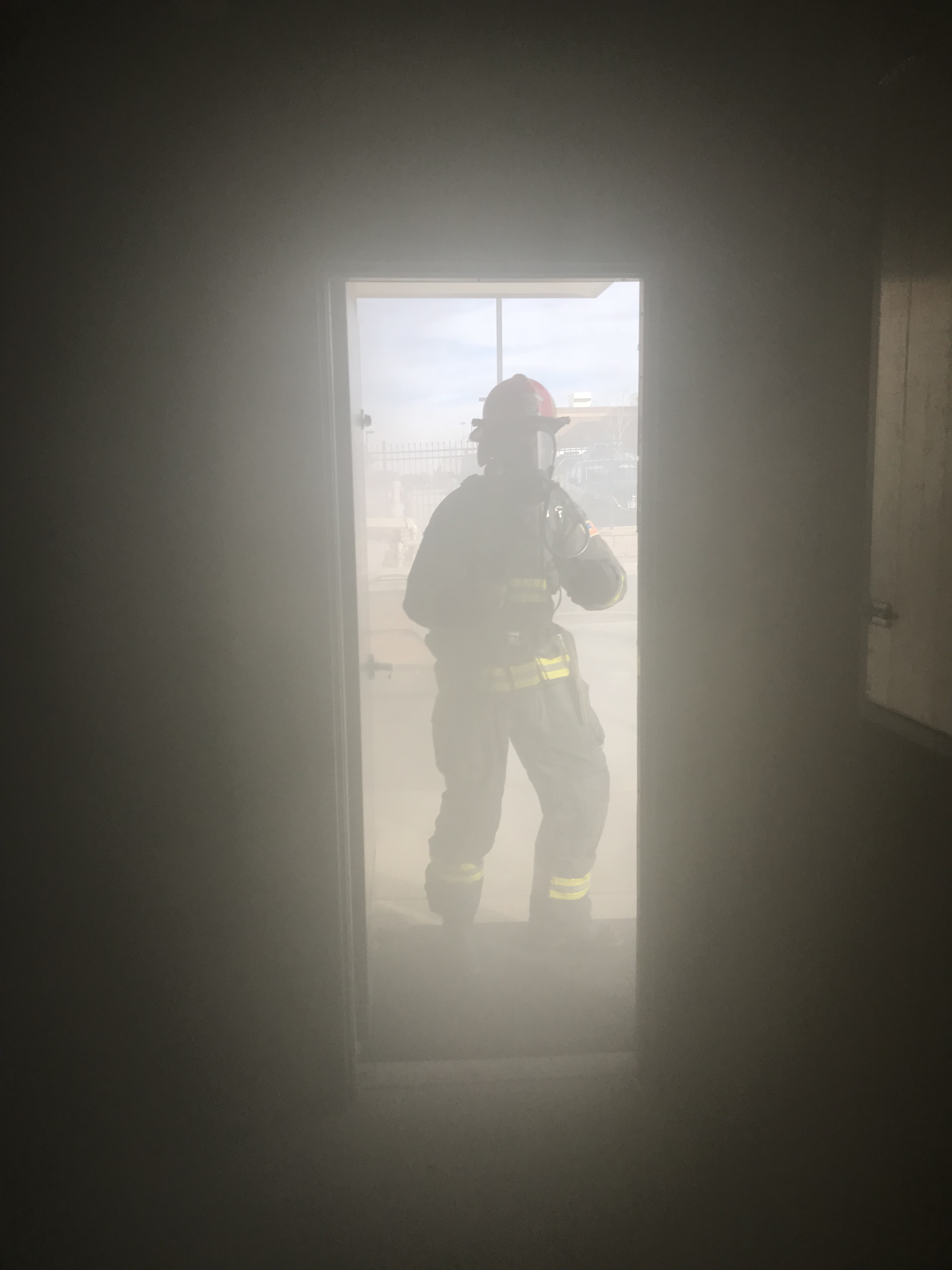 Firefighter standing outside in doorway is almost completely obscured by smoke.