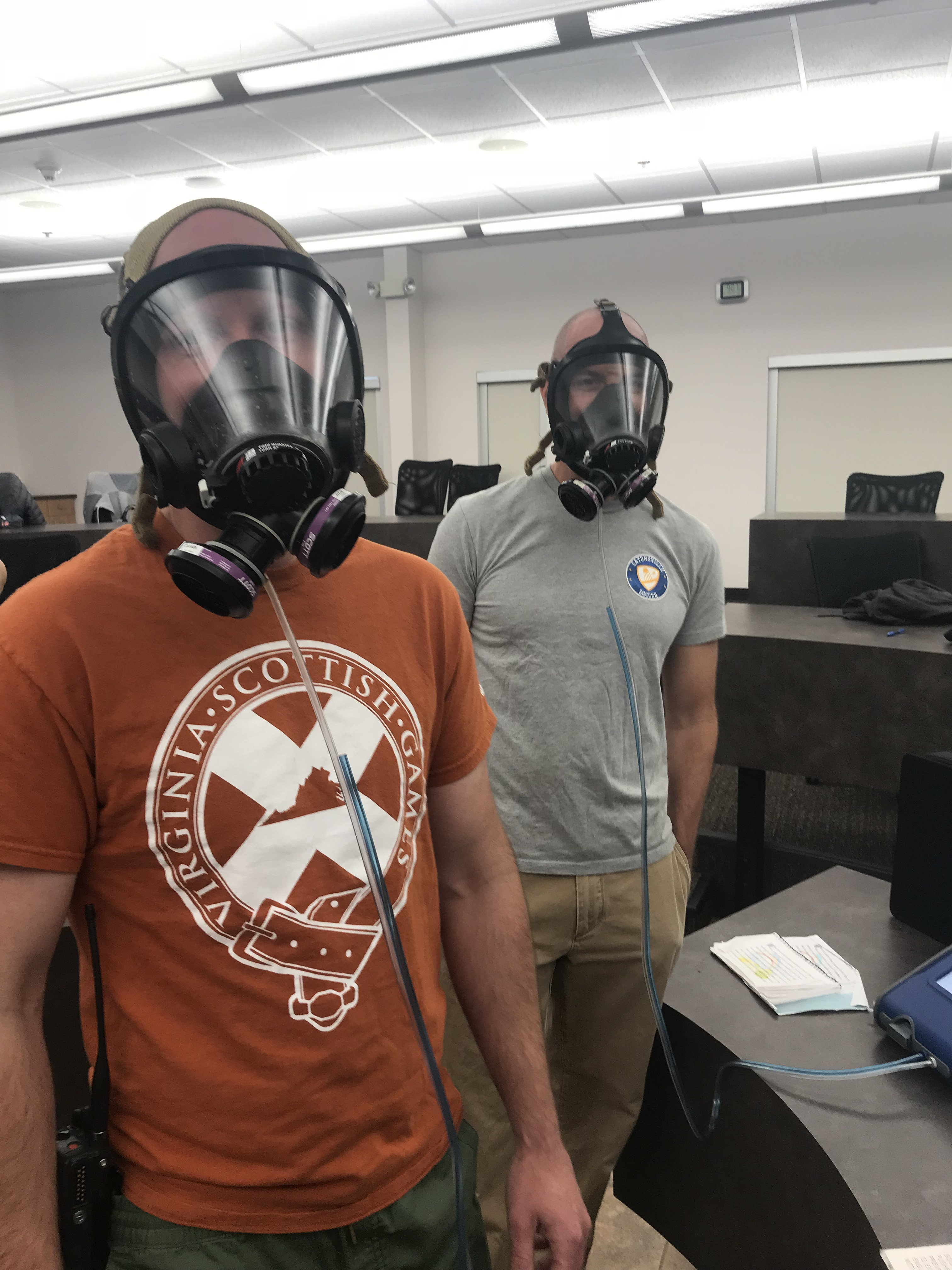 two men wearing SCBA masks hooked up to a respirator