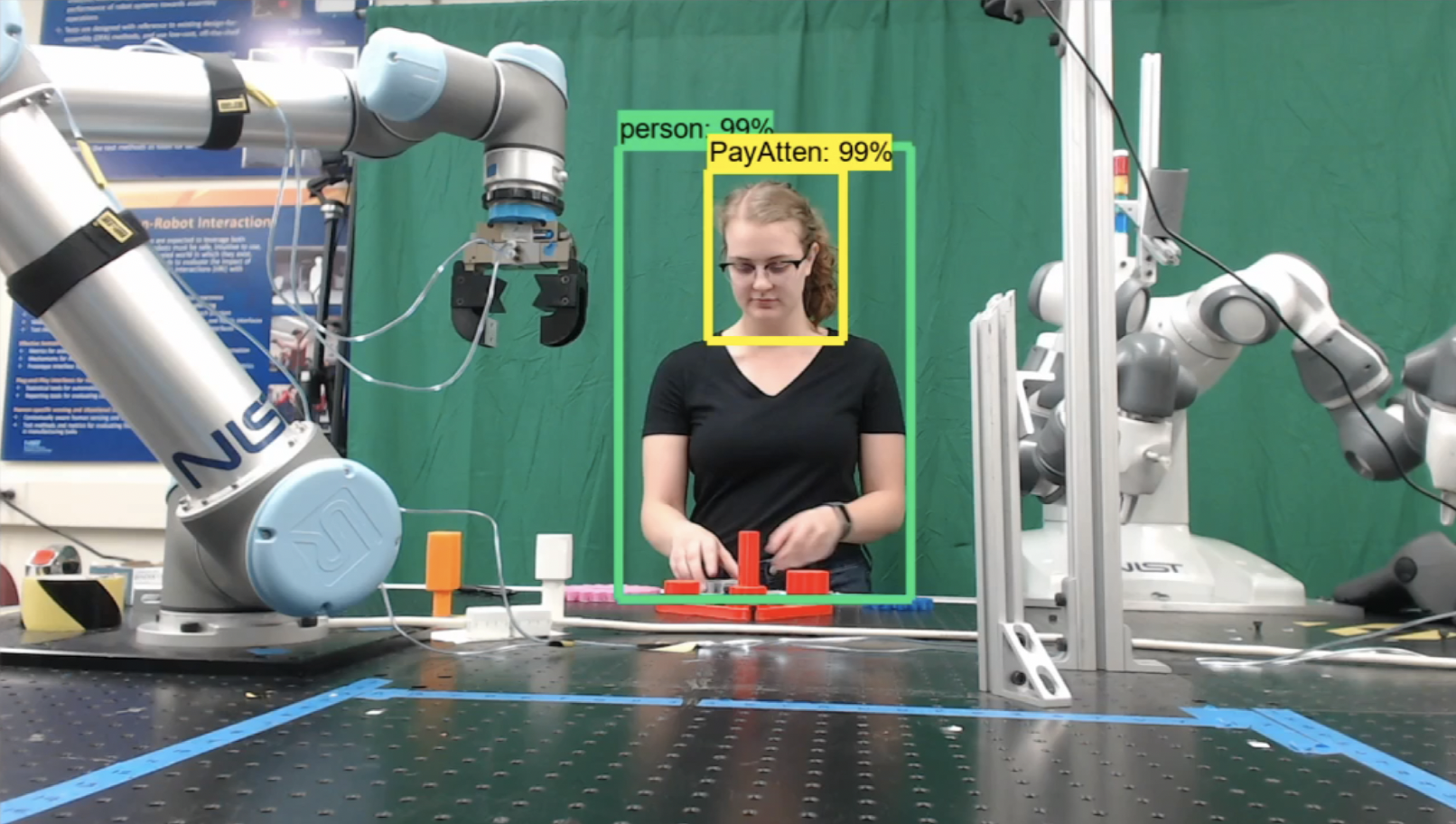 Researcher moves differently shaped and colored plastic blocks on a table as a robotic arm looks on
