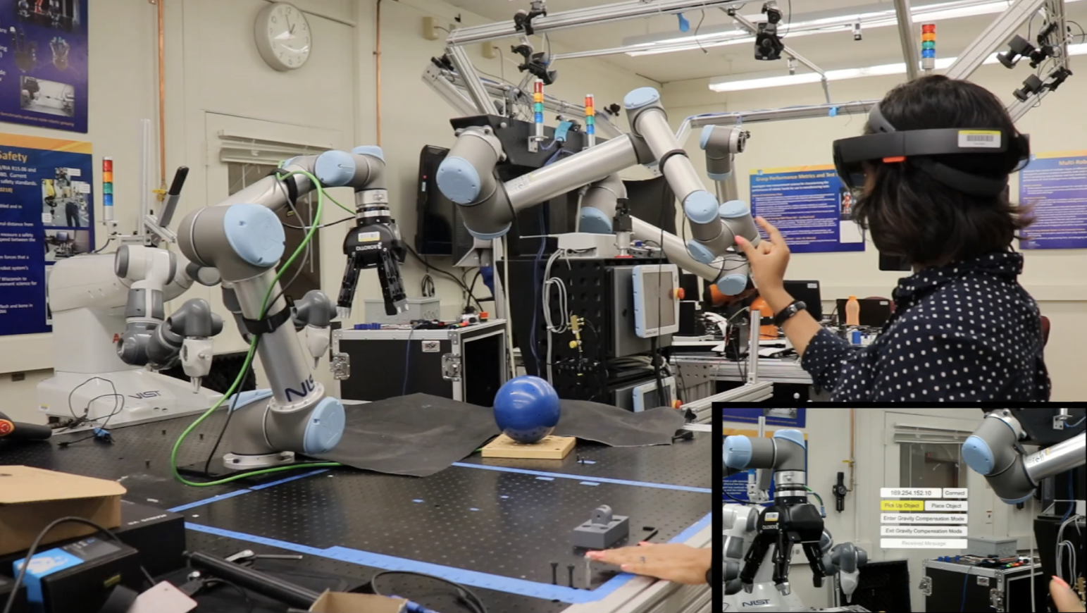 Researcher uses a virtual reality headset to manipulate a robotic arm. In the corner is a box showing the VR headset display, including the IP address, pick up and place object commands, and gravity compensation commands.