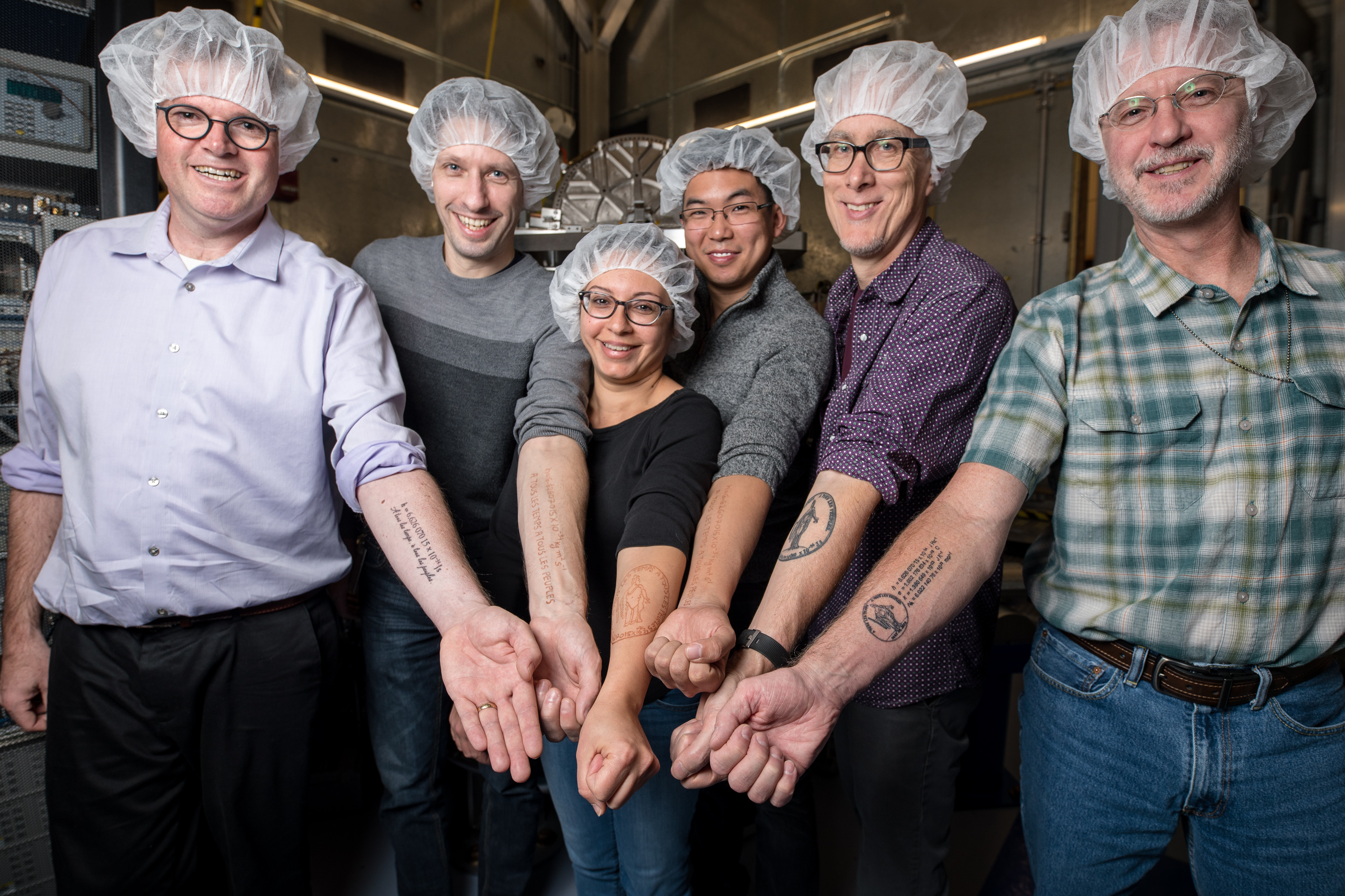 NIST researchers wearing hairnets proudly and happily present their forearms bearing tattoos of the value of the Planck constant