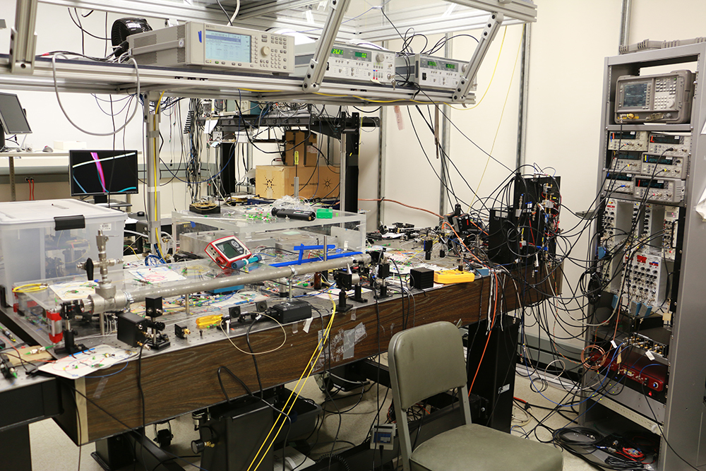picture of a physics lab strewn with wires with a laser table