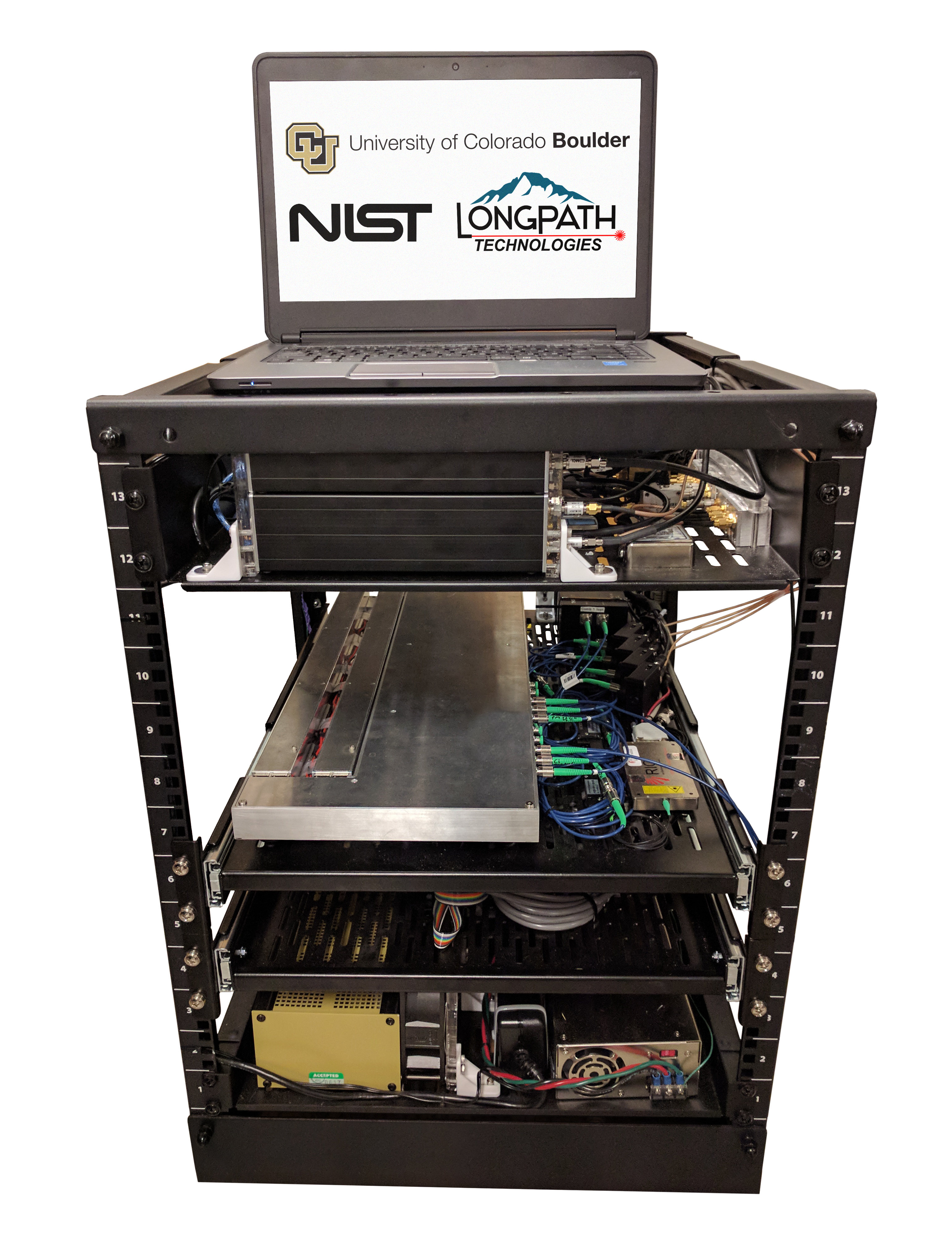 image of the laser frequency comb apparatus, a black metal box with electronics on its shelves and a laptop on top