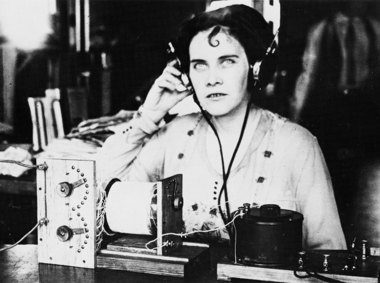 old photo of a woman with a headset on listening to an ancient-looking radio