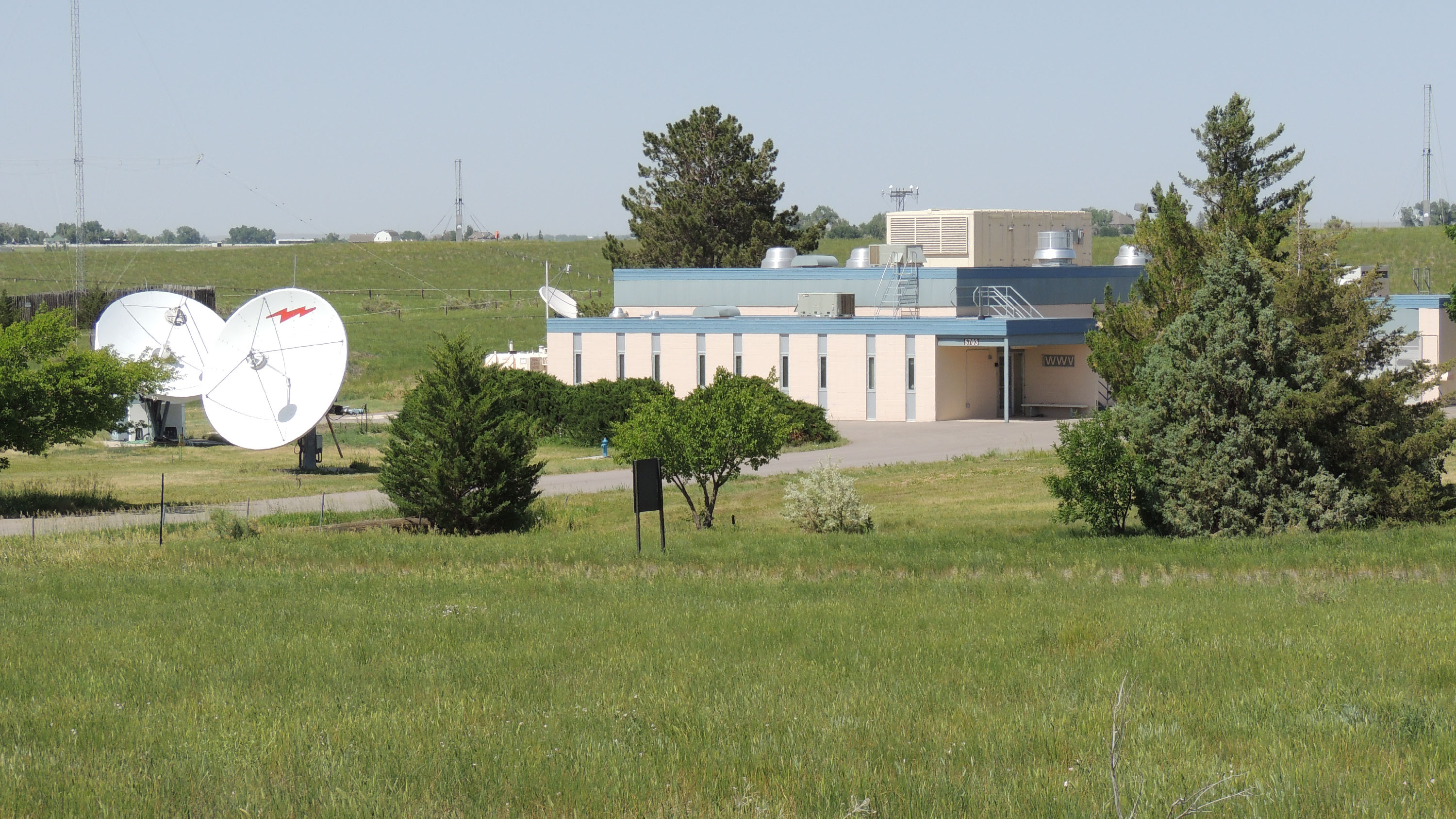 a building in a field with a few trees around it, two big radio dishes at left and some tall radio transmission antennae in the background