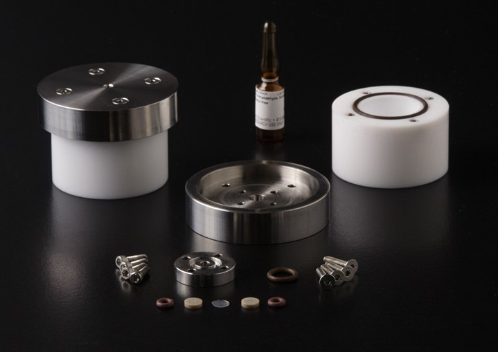 Components of NIST prototype formaldehyde emission reference material. Two white cylinders, two steel endcaps, screws, washers, and membranes