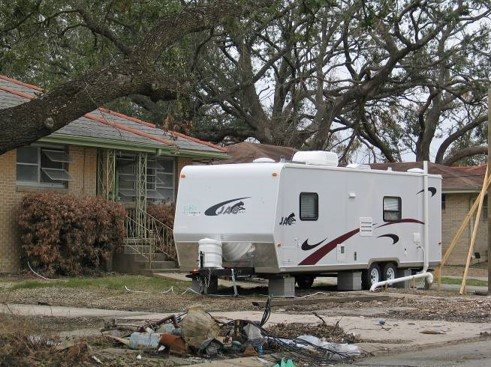 mobile trailer parked on the front lawn of a house damaged by Hurricane Katrina