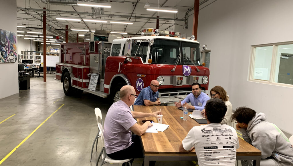 This image shows a group of people sitting around a wooden table with a firetruck behind them