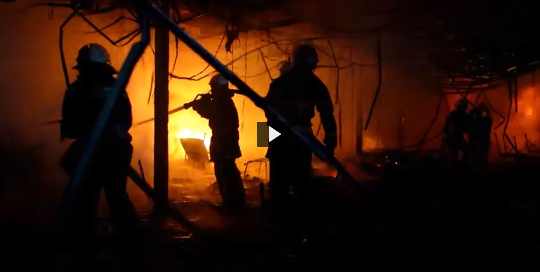 Screenshot of a video in which we see a silhouette of firefighters responding to a burning fire