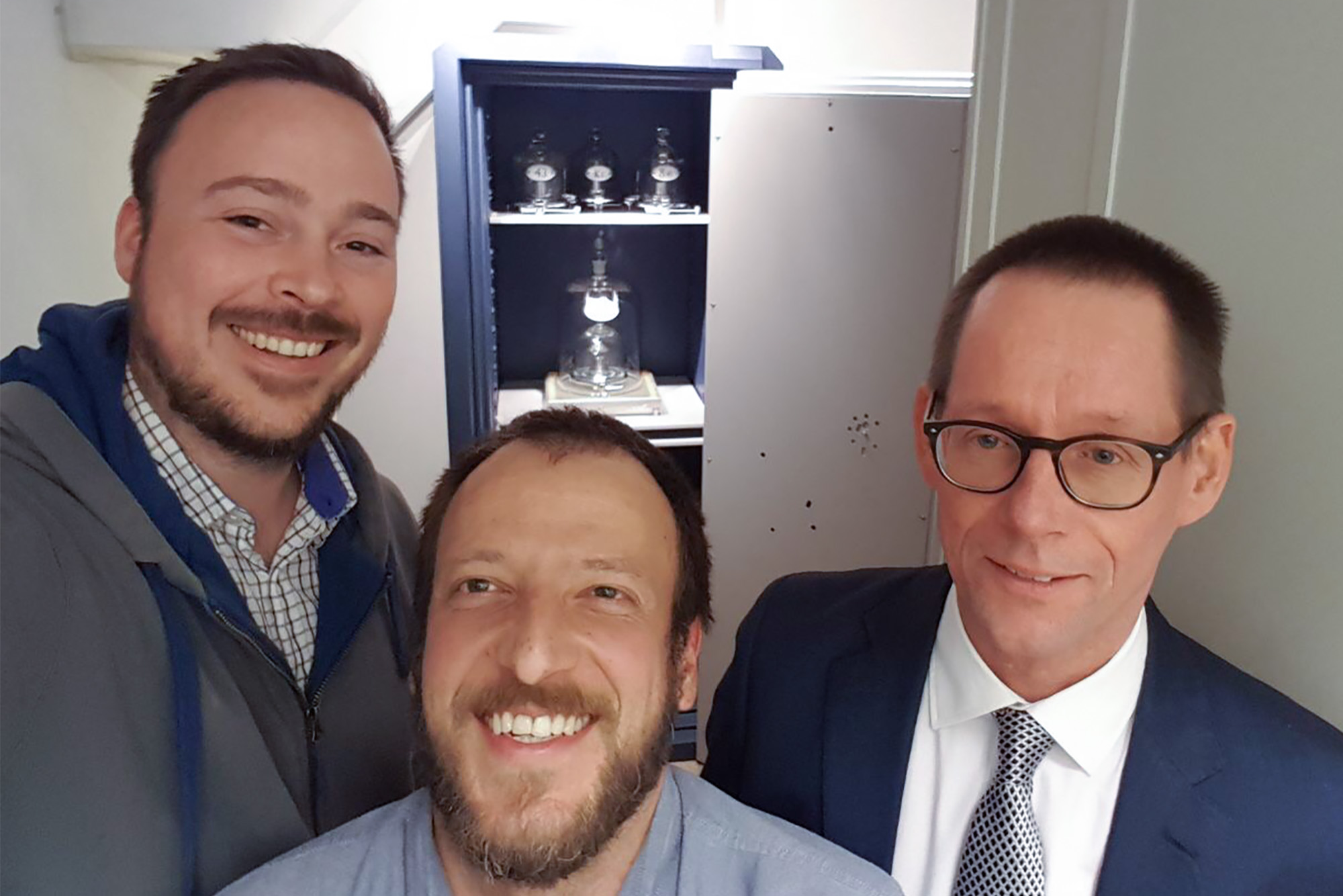 three men take a selfie inside the kilogram vault. The kilogram is visible in a safe behind them.