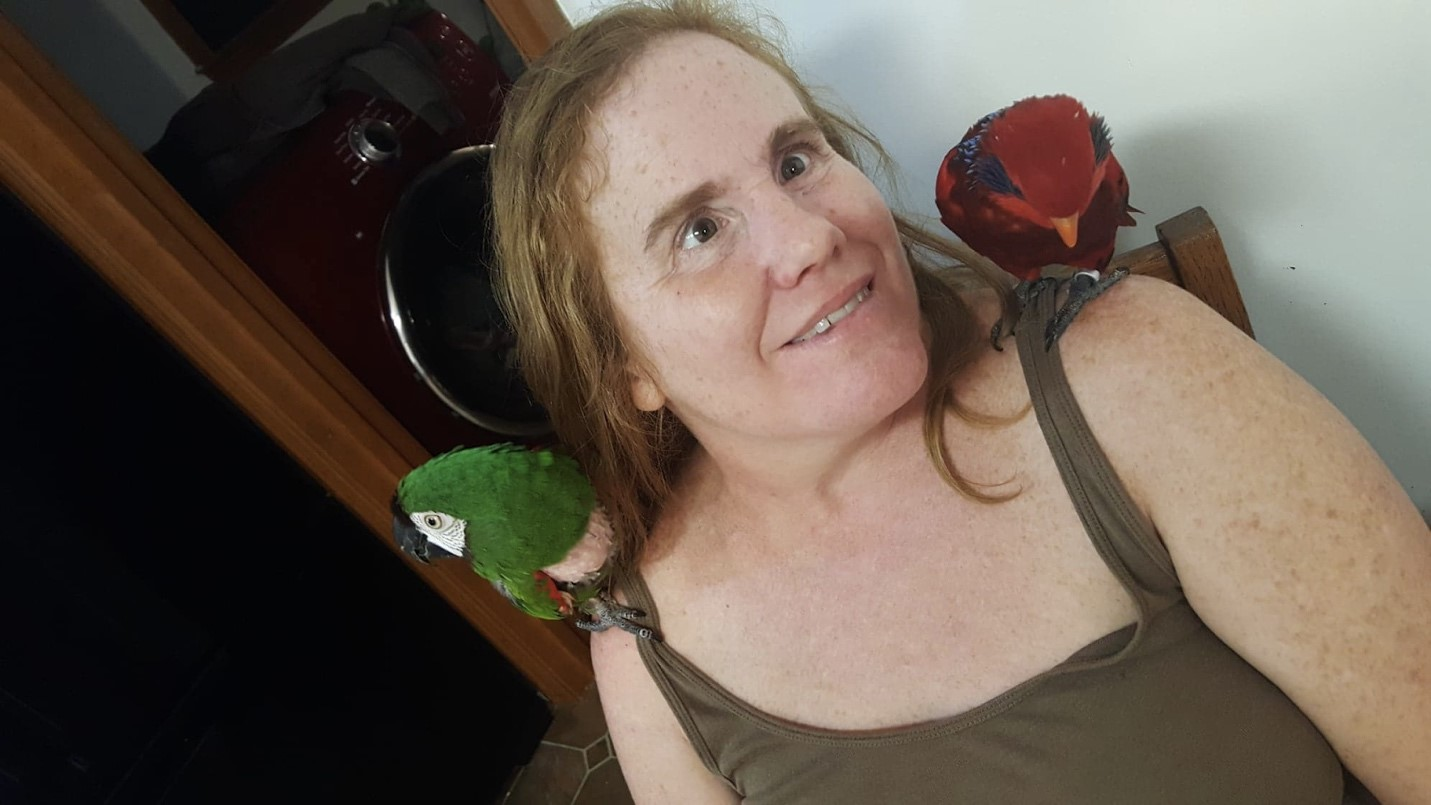Mrs. Hidle and her birds, Ned, a green parrot, sits on her right shoulder, while Mimi, a red parrot, sits on her left