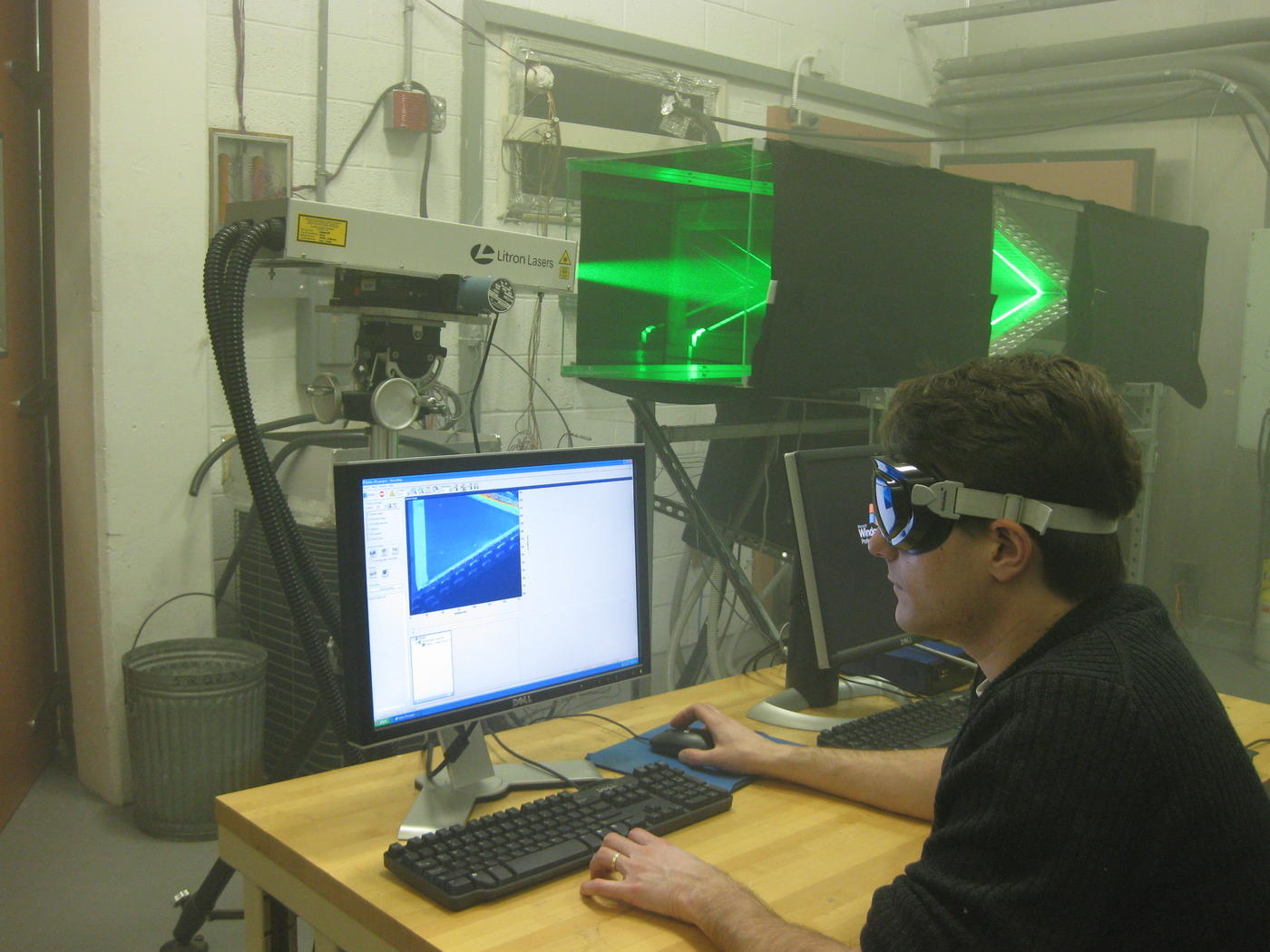 Photo of NIST scientist using Particle Image Velocimetry to measure the air flow distribution through a heat pump component.