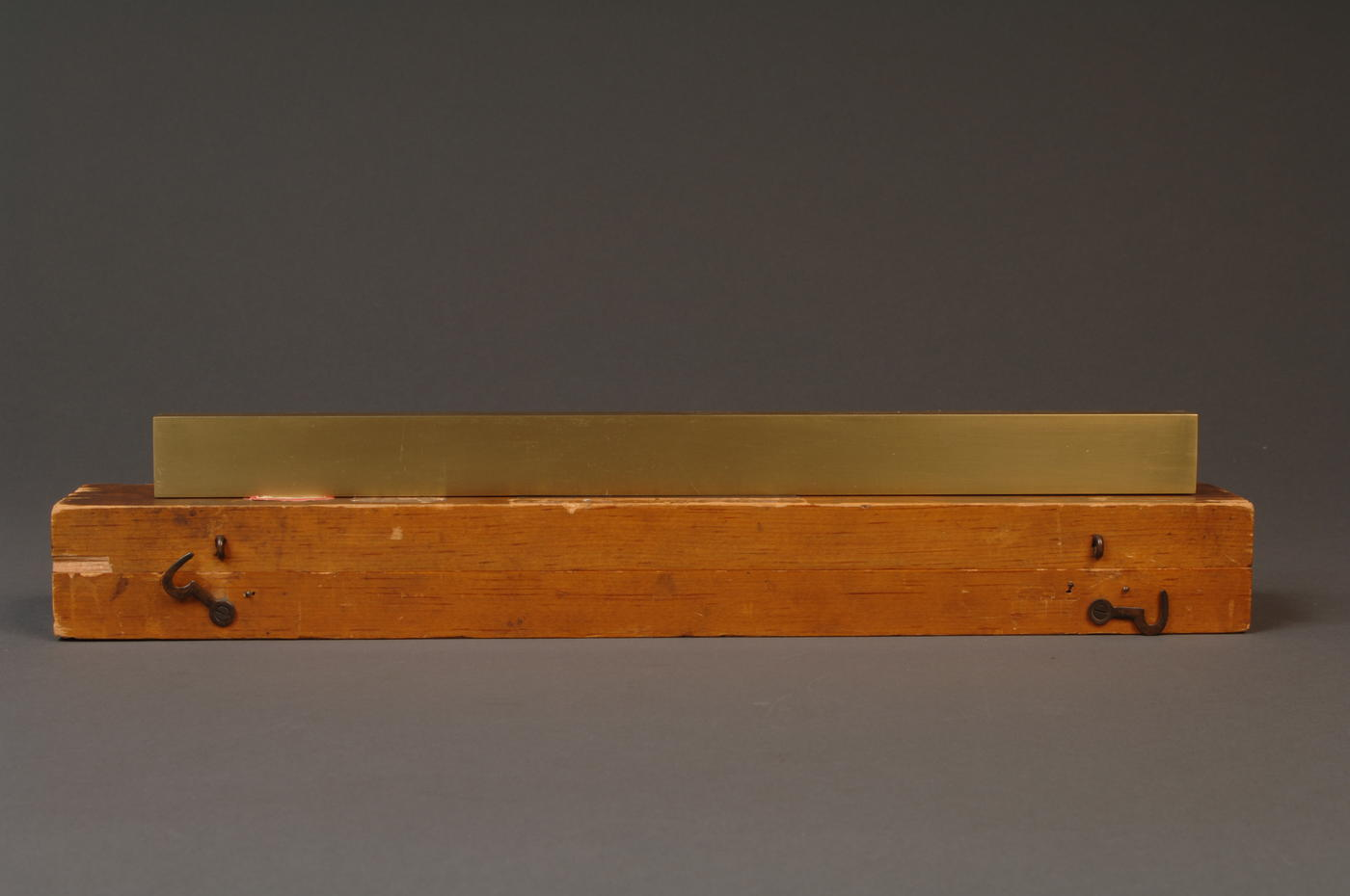 Brass line scale sitting on top of wooden box