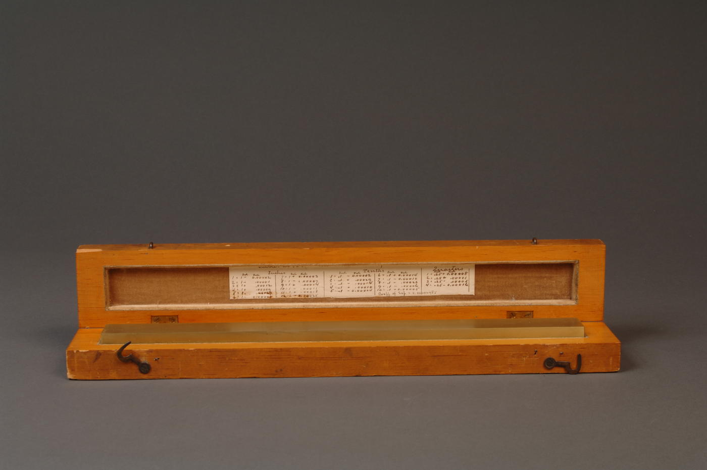 Brass line scale sitting in wooden box with lid open, calibration writing visible on side of lid.