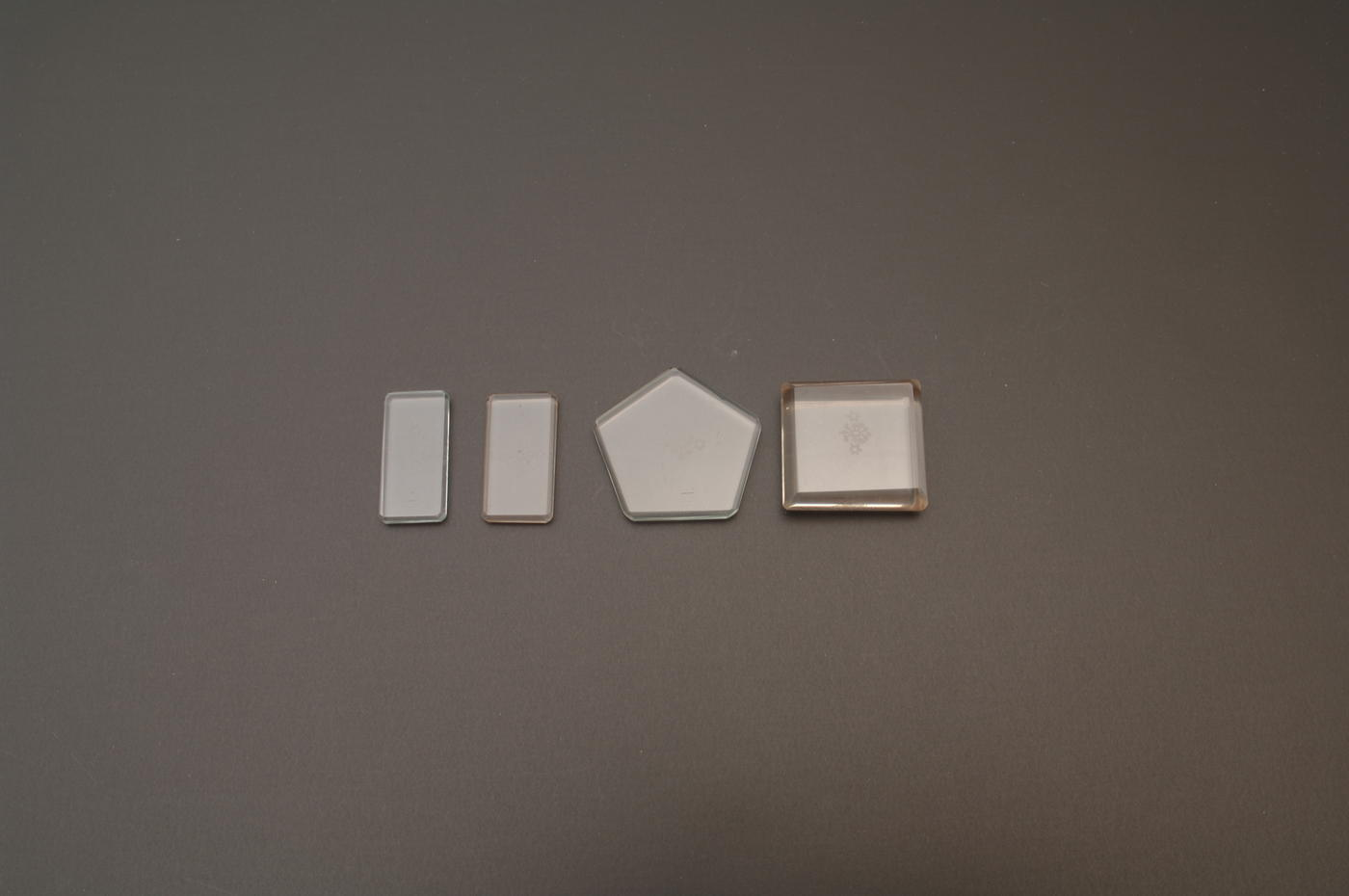 Set of 4 small solid glass weights in rectangle and pentagon shapes