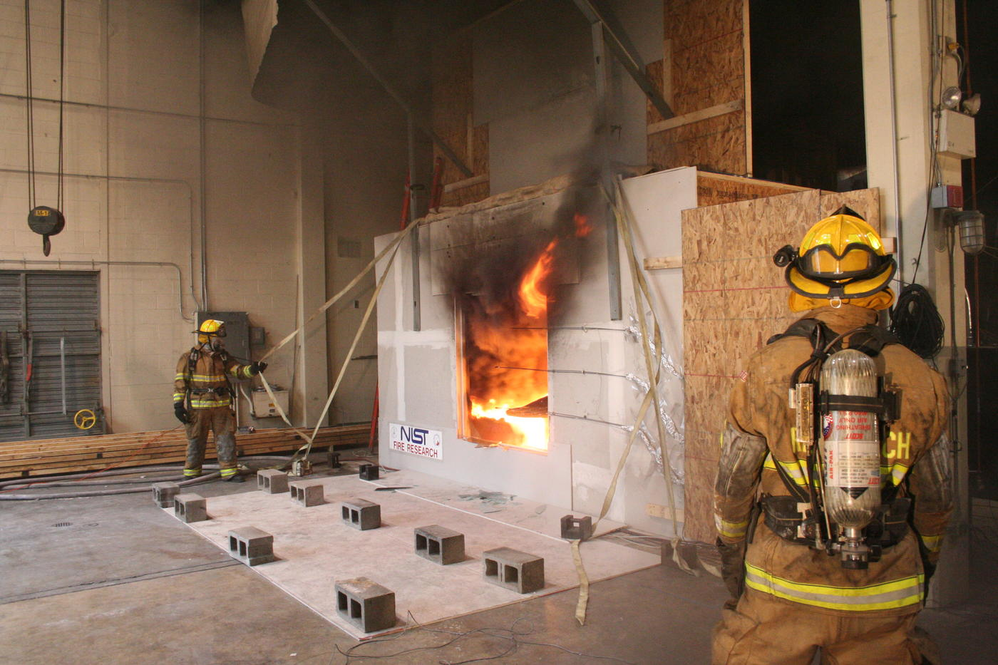 Firefighters outside a NIST test facility for examining  the impact of wind on fire spread