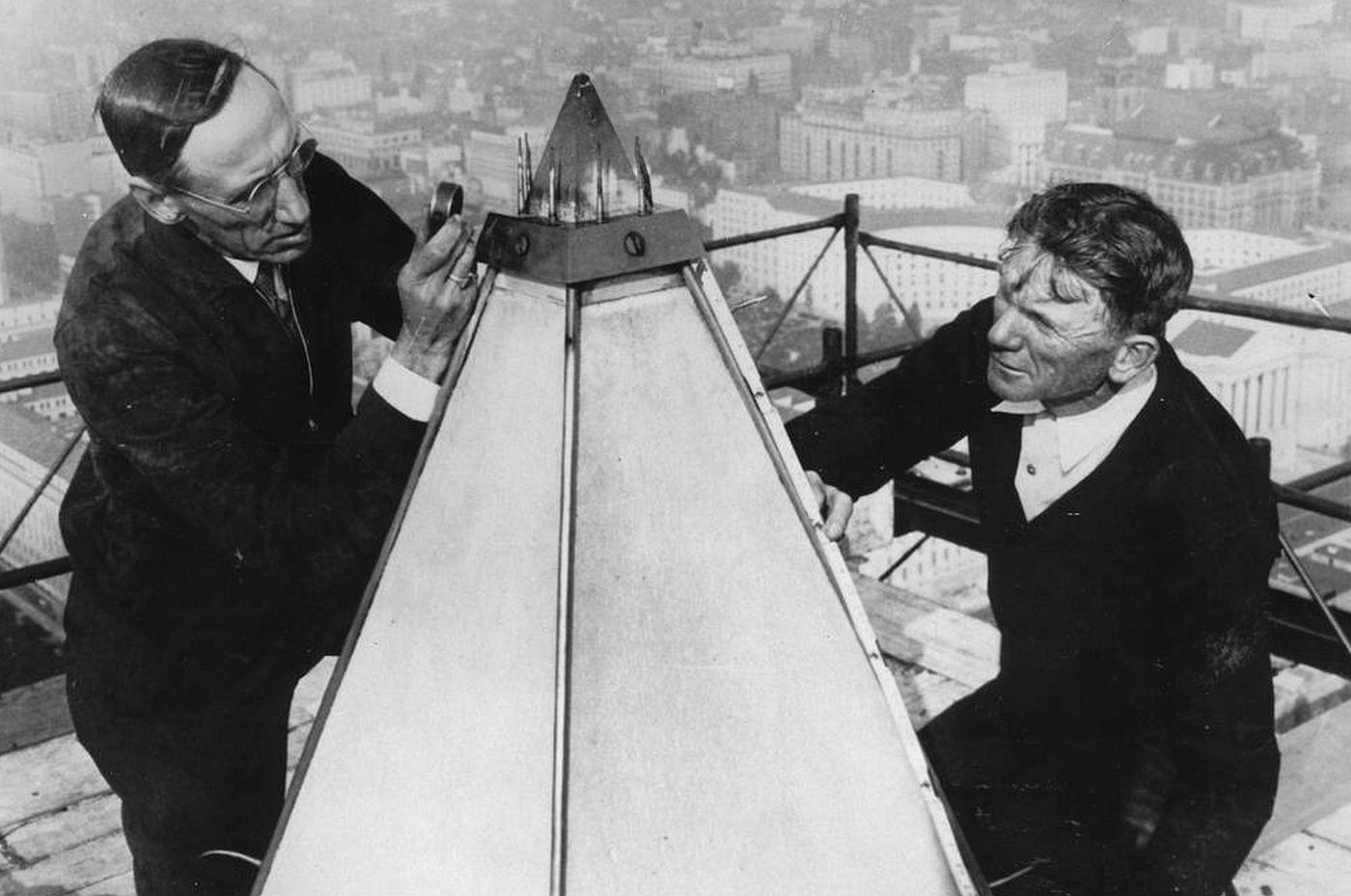 Two men sit on scaffolding and examine the tip of the Washington Monument.
