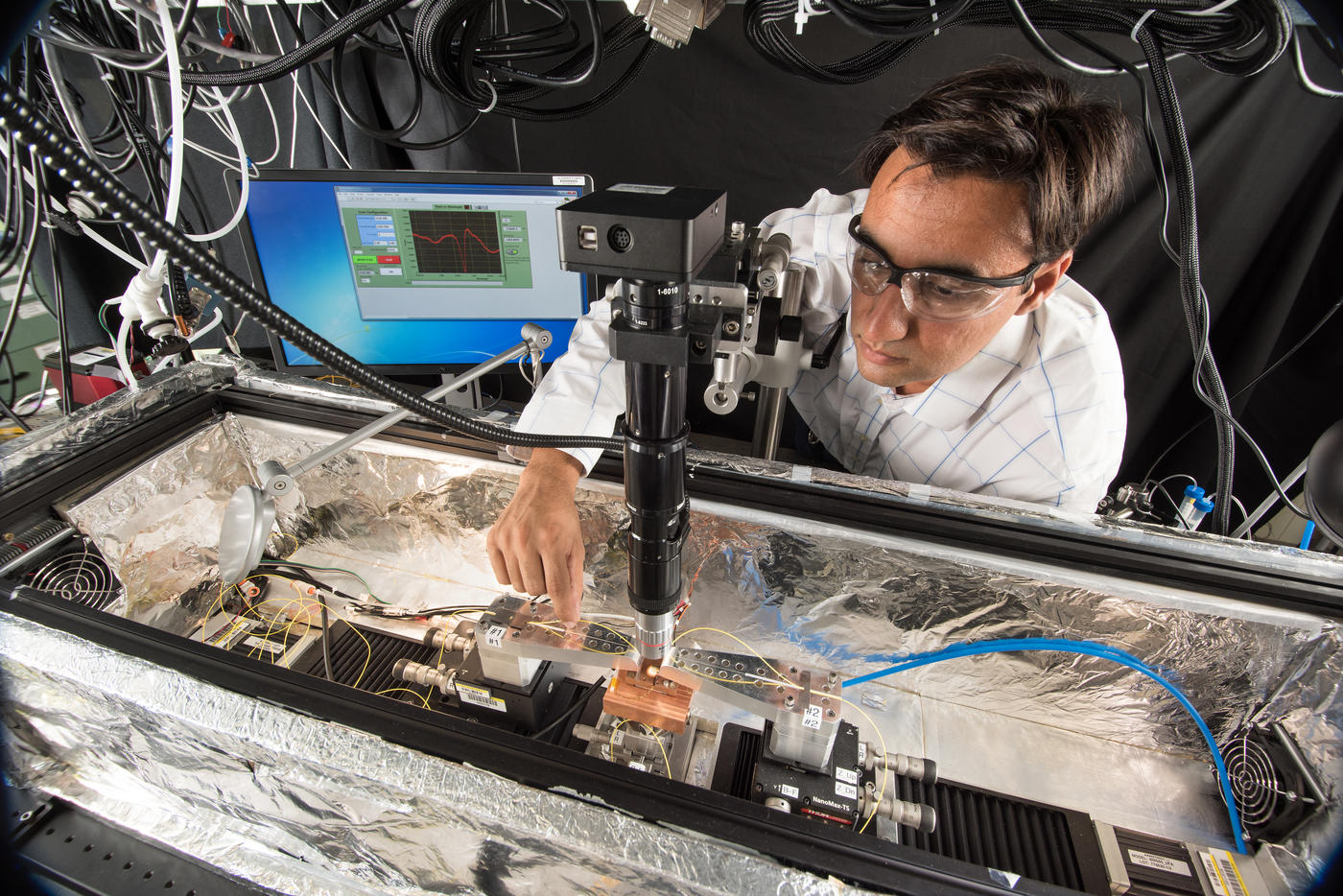 Scientist stands at a photonics optical probe station.