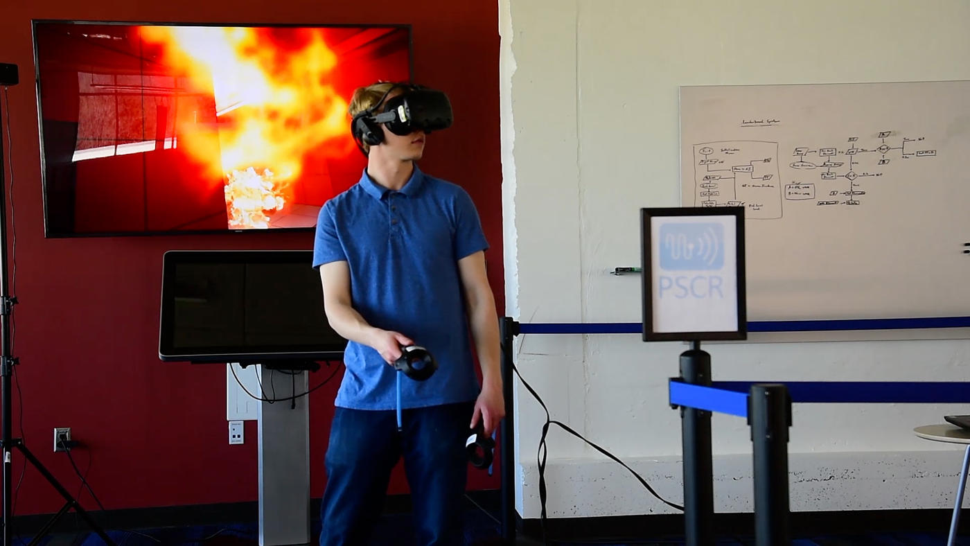 Person wearing a VR headset and holding controllers. Behind him a screen shows what the researcher is seeing within the headset--a virtual office building that is on fire.