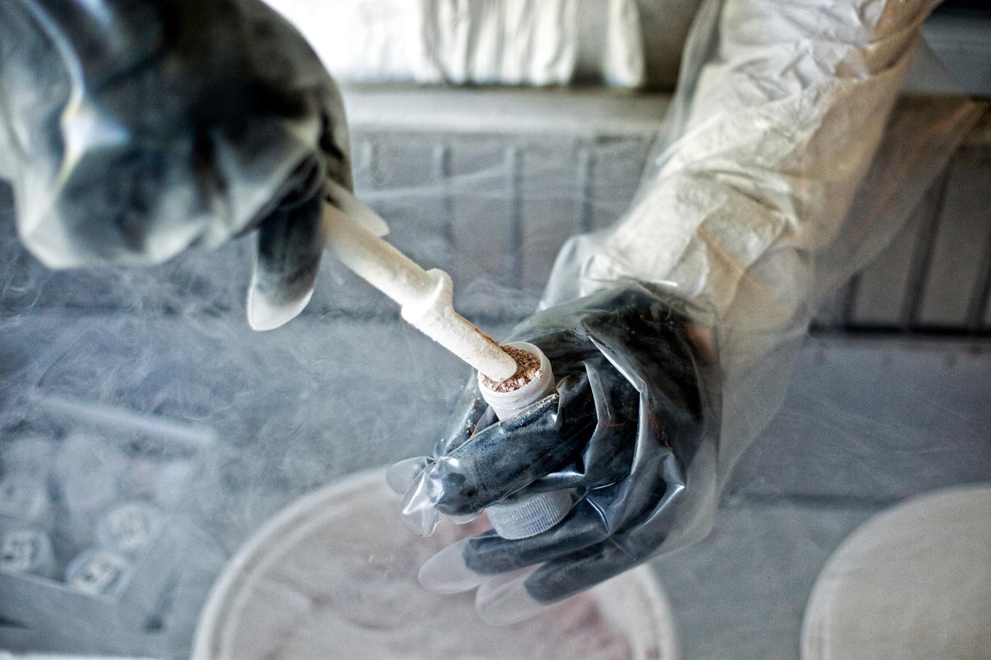 A pair of gloved hands prepares a specimen for storage using a test tube and a special, slim scoop.
