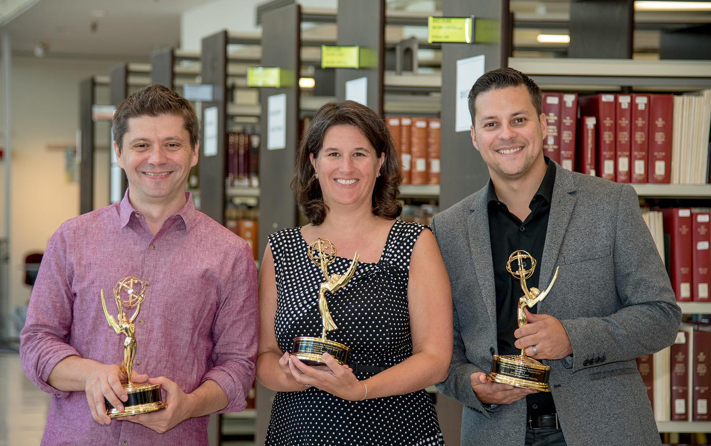 three people hold Emmy Awards in the NIST library