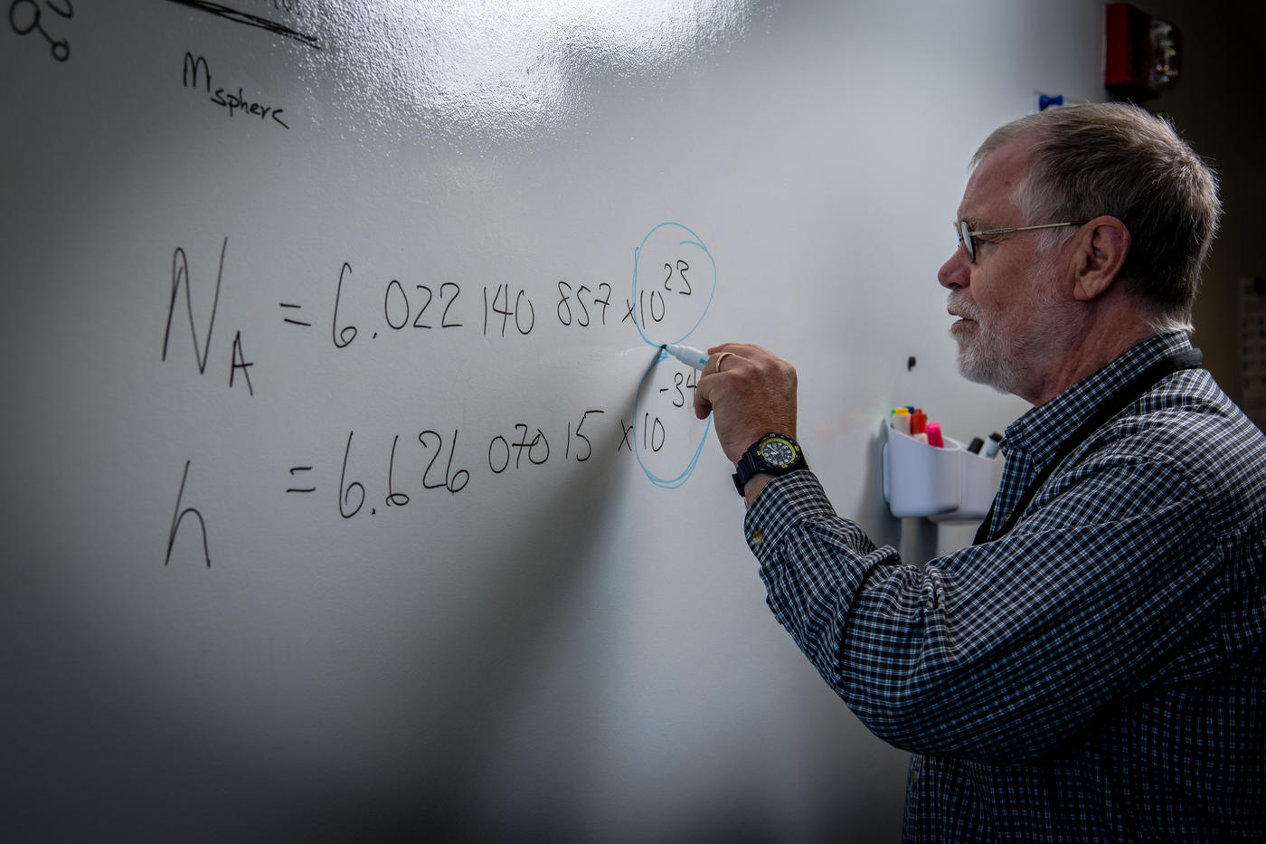 Chemist Bob Vocke stands in front of a white board writing out several complicated equations related to the mole redefinition.