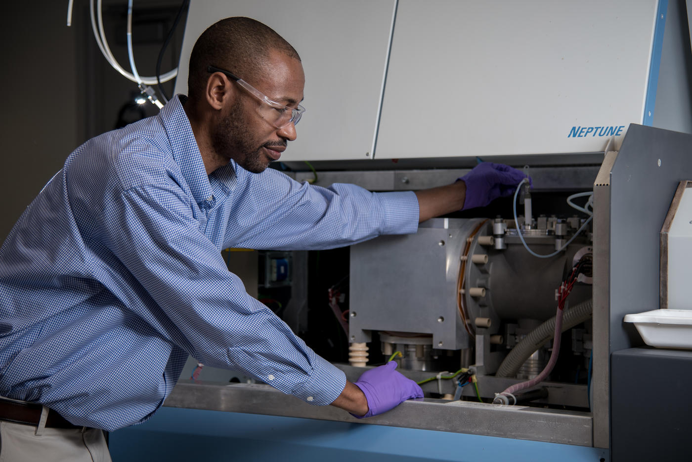 Chemist Savelas Rabb is bent over slightly, using a tool to check on the settings inside of a large instrument known as a mass spectrometer.