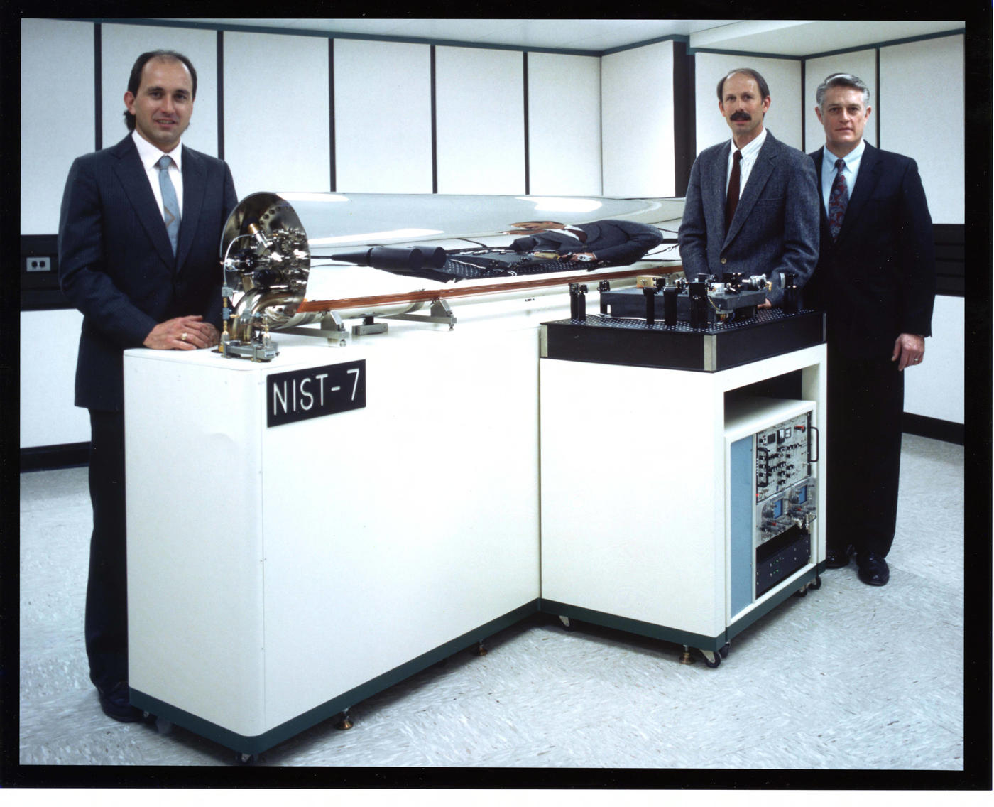 Three men stand behind a glass tube with equipment inside