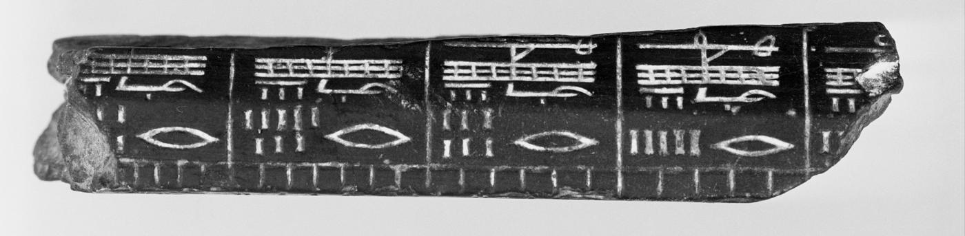 piece of black rock with white Egyptian markings