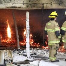 Two firefighters look over the last flames inside a compartment where the flammability of cross-laminated timber buildings is being tested.